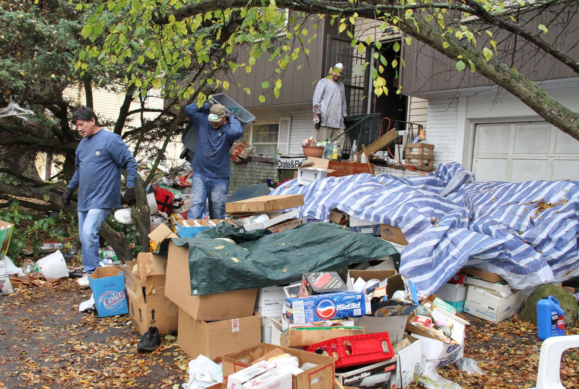 Workers from Junk King remove items Tuesday from John Wuerffel's front yard and home on Hampton Lane in Schaumburg. The work is being done as part of a court-ordered cleanup.