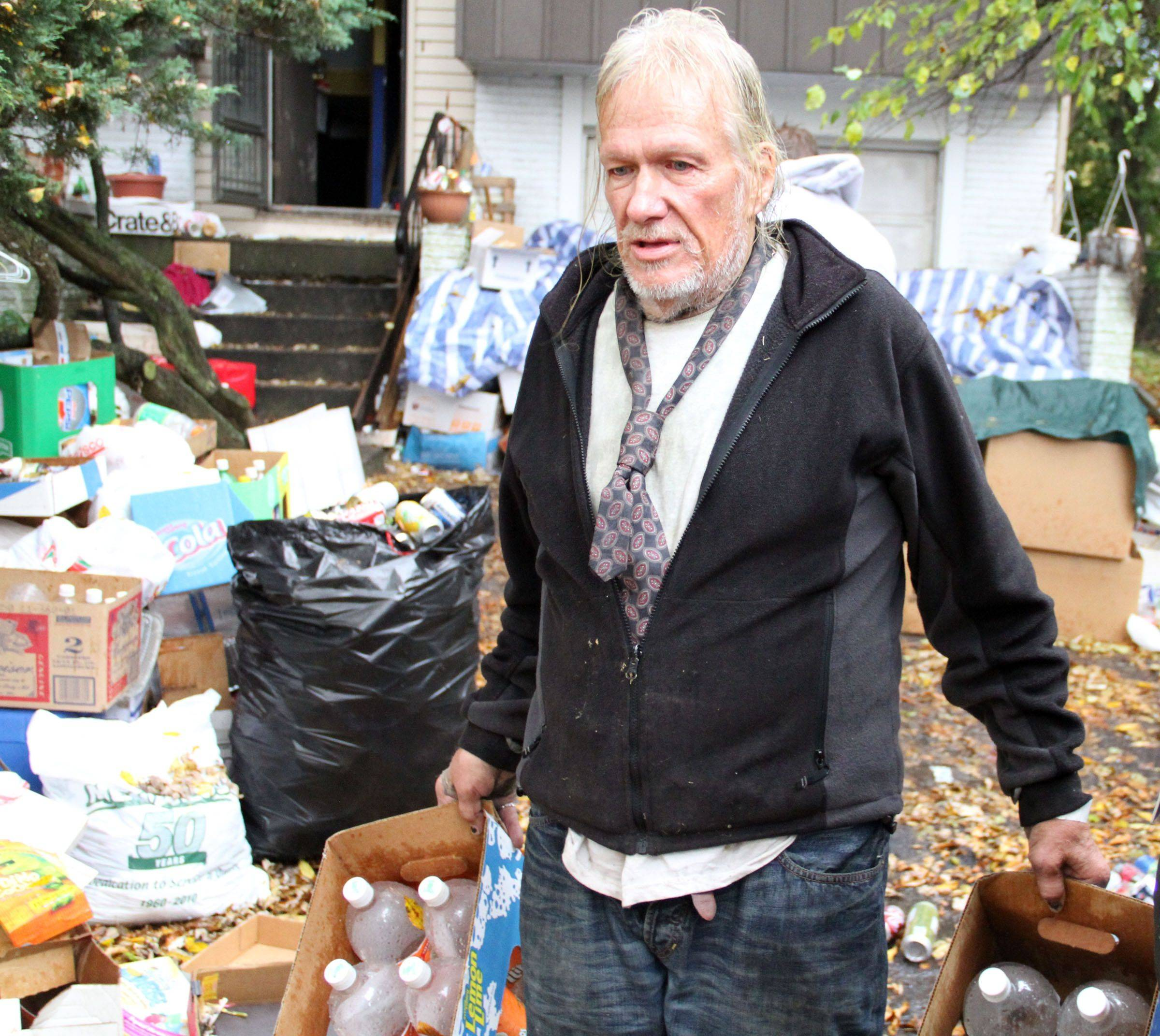 John Wuerffel gathers recycled items that he is trying to save as workers from Junk King remove items from his house, backyard, and front yard on Hampton Lane in Schaumburg.
