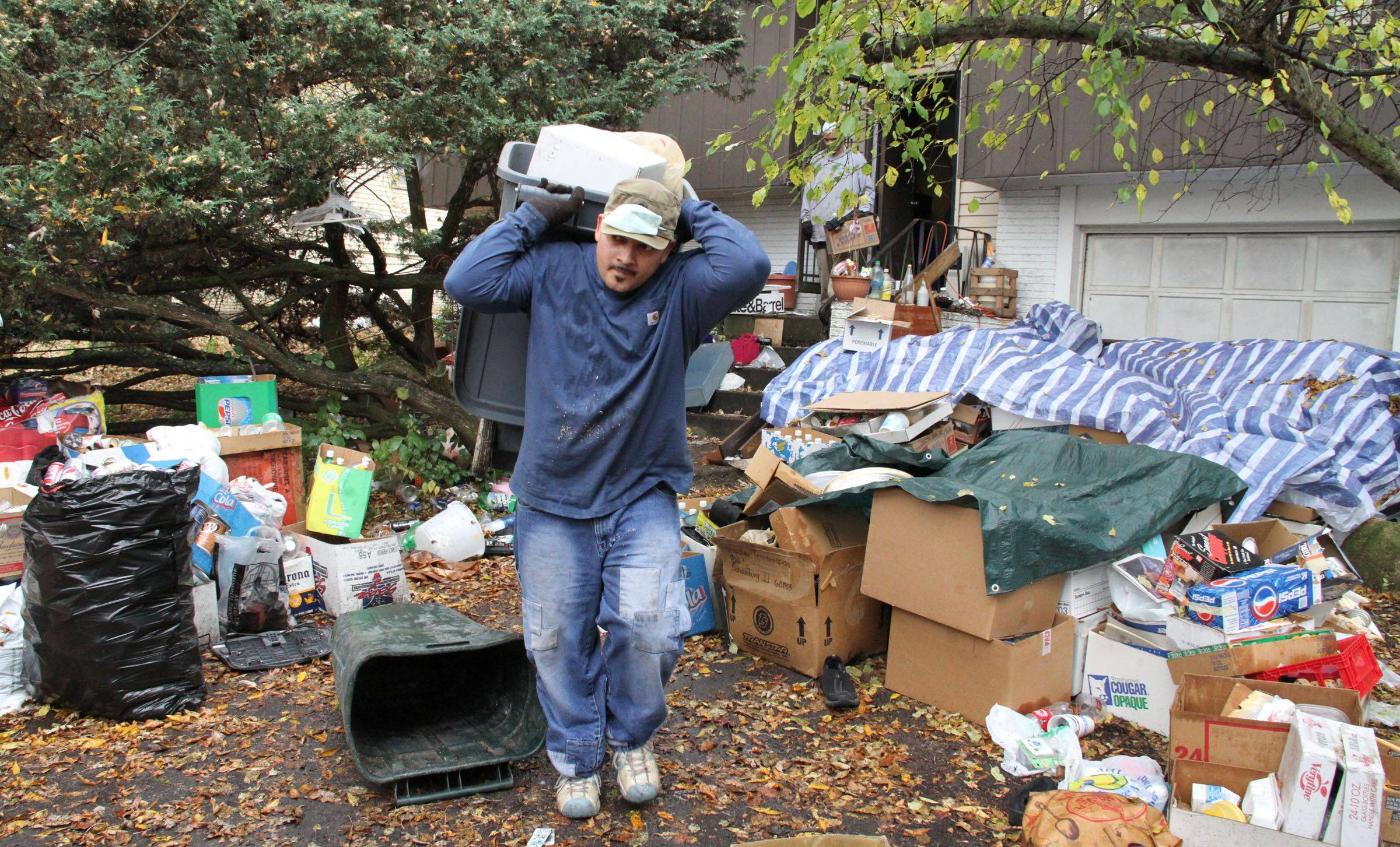 Workers with Junk King began removing plastic, cardboard and other rubbish from the Schaumburg home of John Wuerffel on Wednesday morning.