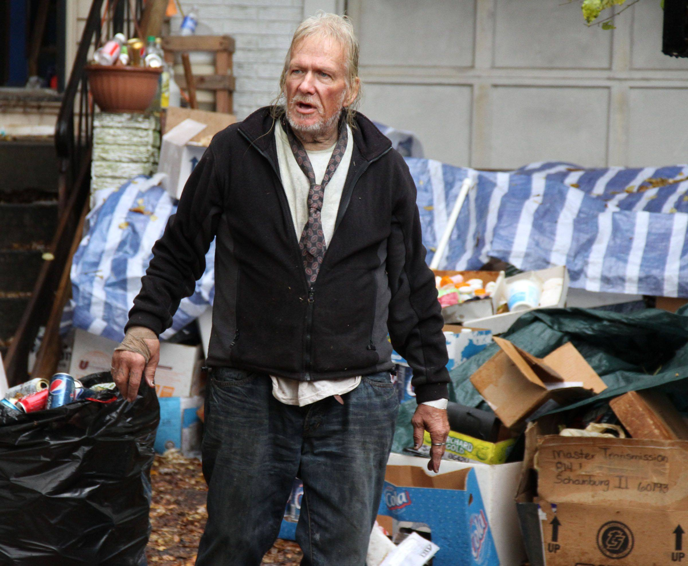 John Wuerffel gathers recycled items he is trying to save as workers from Junk King remove items from his house, backyard, and front yard on Hampton Lane in Schaumburg