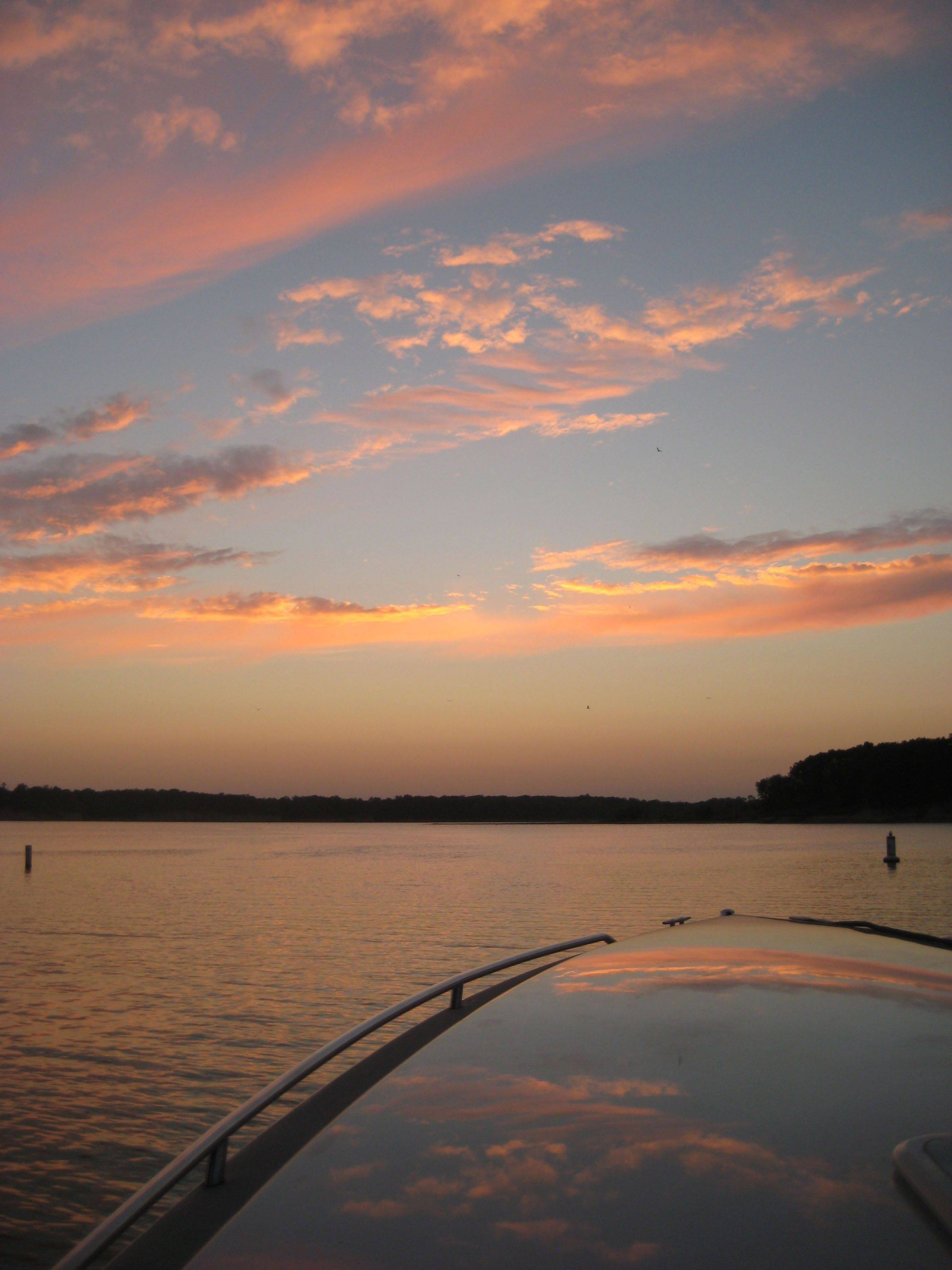 The warm hues of the sunset reflect on the nose of a boat at Lake Shelbyville in Sullivan.