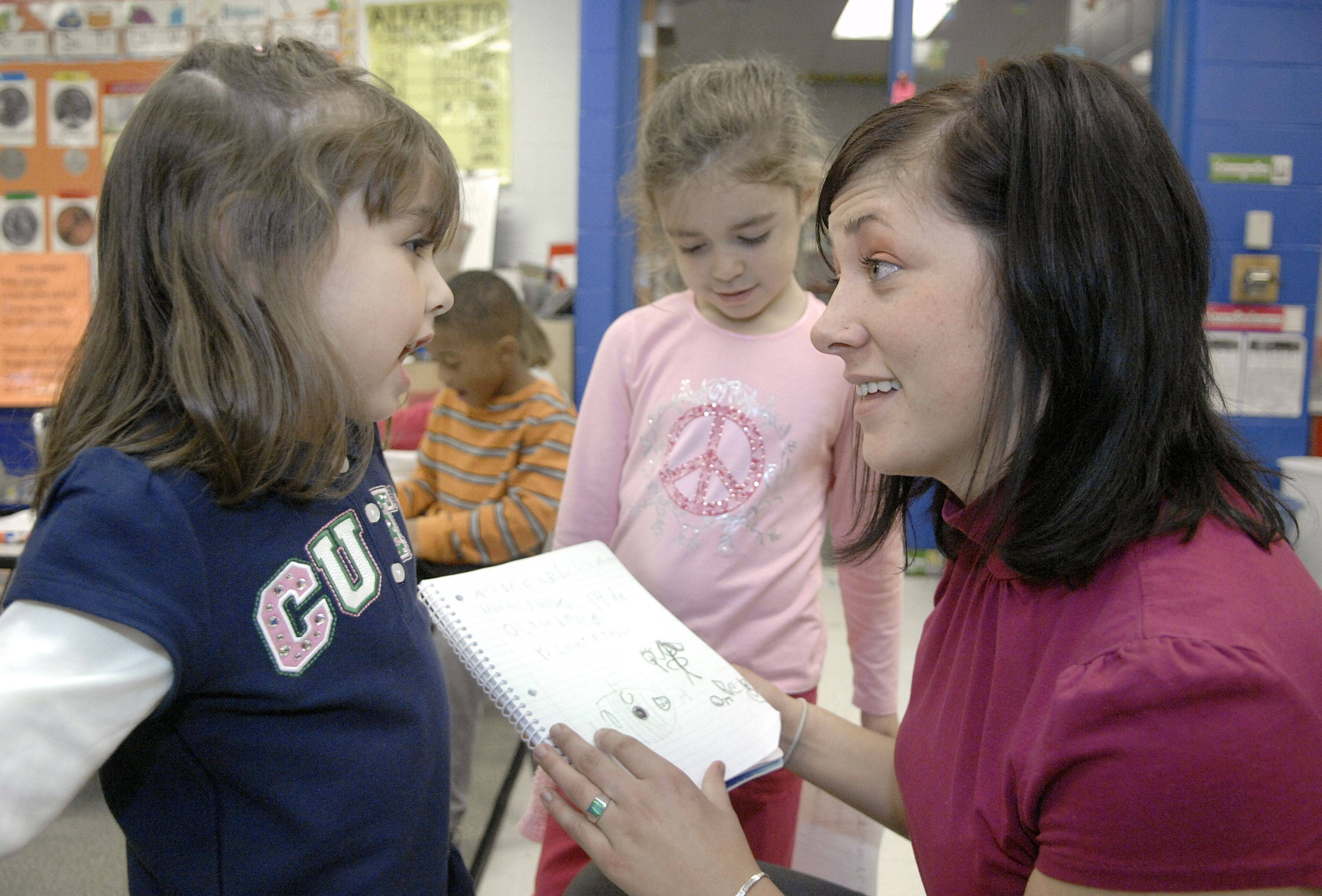Judson University student Kristen Semrich of Lake in the Hills asks Andrea Llavona what she drew in her journal during Imelda Callazo's kindergarten class at Liberty Elementary School in Carpentersville. Classmate Sarina Simonelli waits her turn. Semrich, who is studying elementary education, helps in the bilingual class a few times a week.
