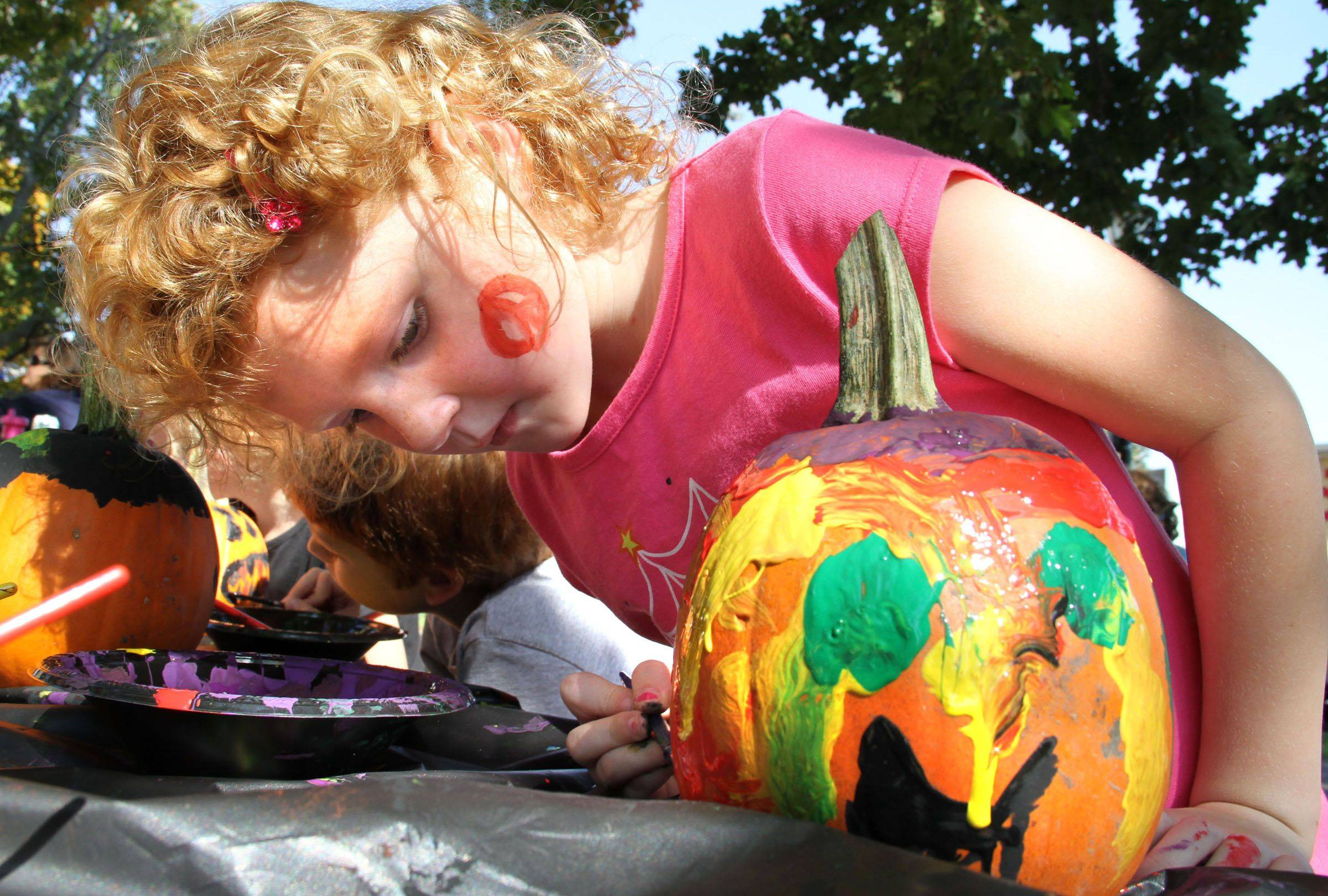 Lindsay Crowther, 5, of Gurnee, paints a pumpkin at the pumpkins, pictures and live entertainment family event Saturday at Cook Park in Libertyville.