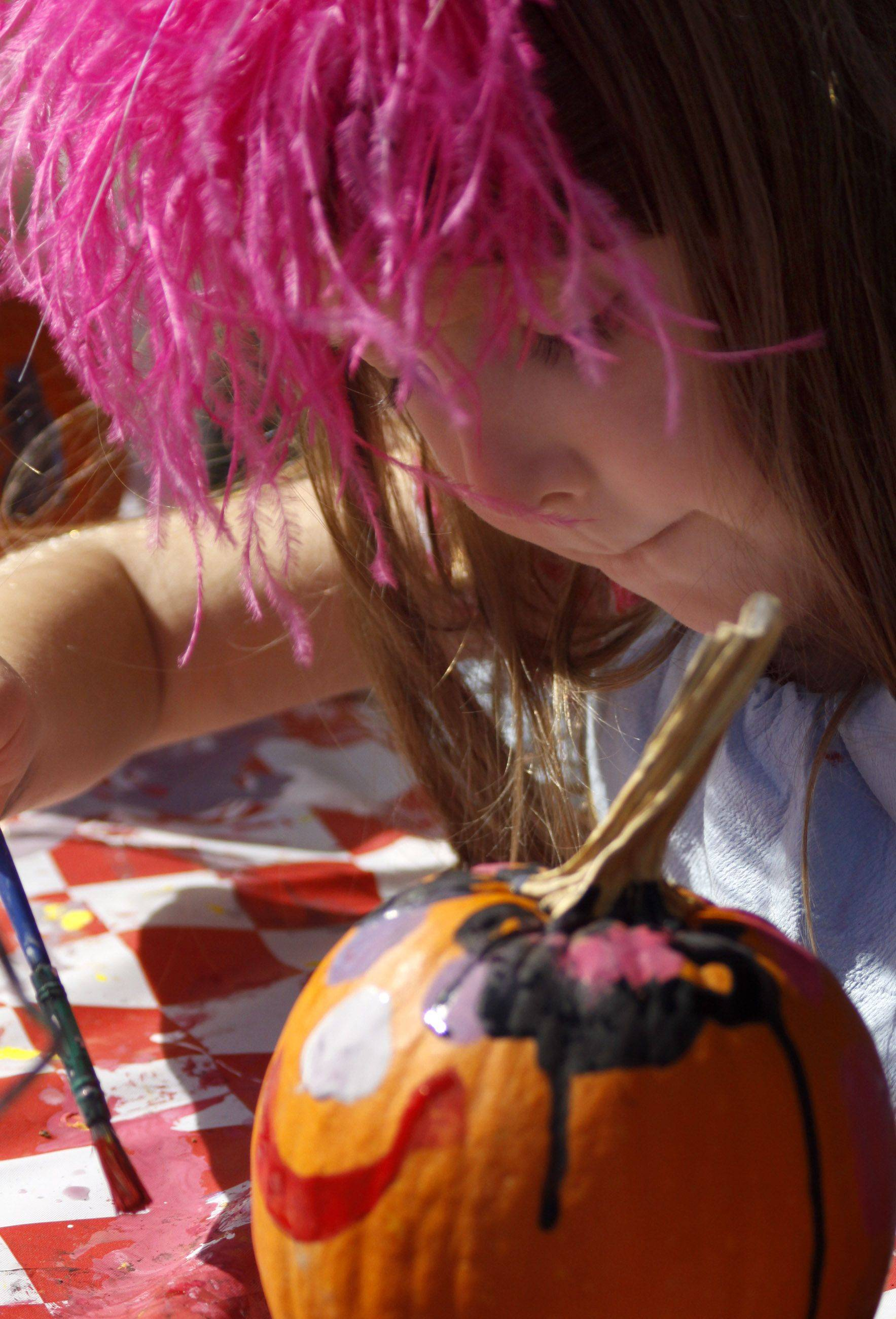 Jayde Grant, 5, of Naperville puts the finishing touches on her pumpkin at the Danada Fall Festival Sunday at Danada Equestrian Center.