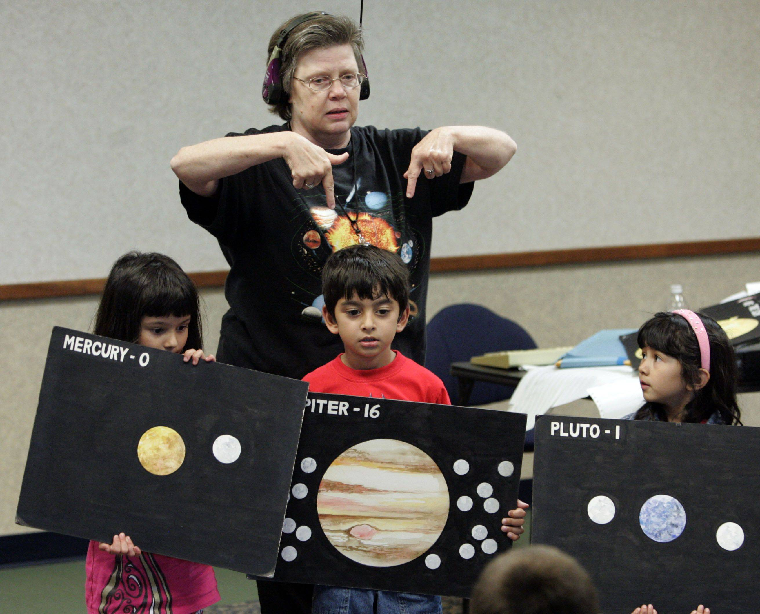 Actor Mary Heitert of Carol Stream with The Mystery Shop helps kids solve the mystery of the missing moon with the help of Jasmine Khaytin, 7 of Barrington, left, Morya Odak, 6 of Mundelein and Shaina Khaytin, 5 of Barrington during a program at Fremont Public Library Monday afternoon.
