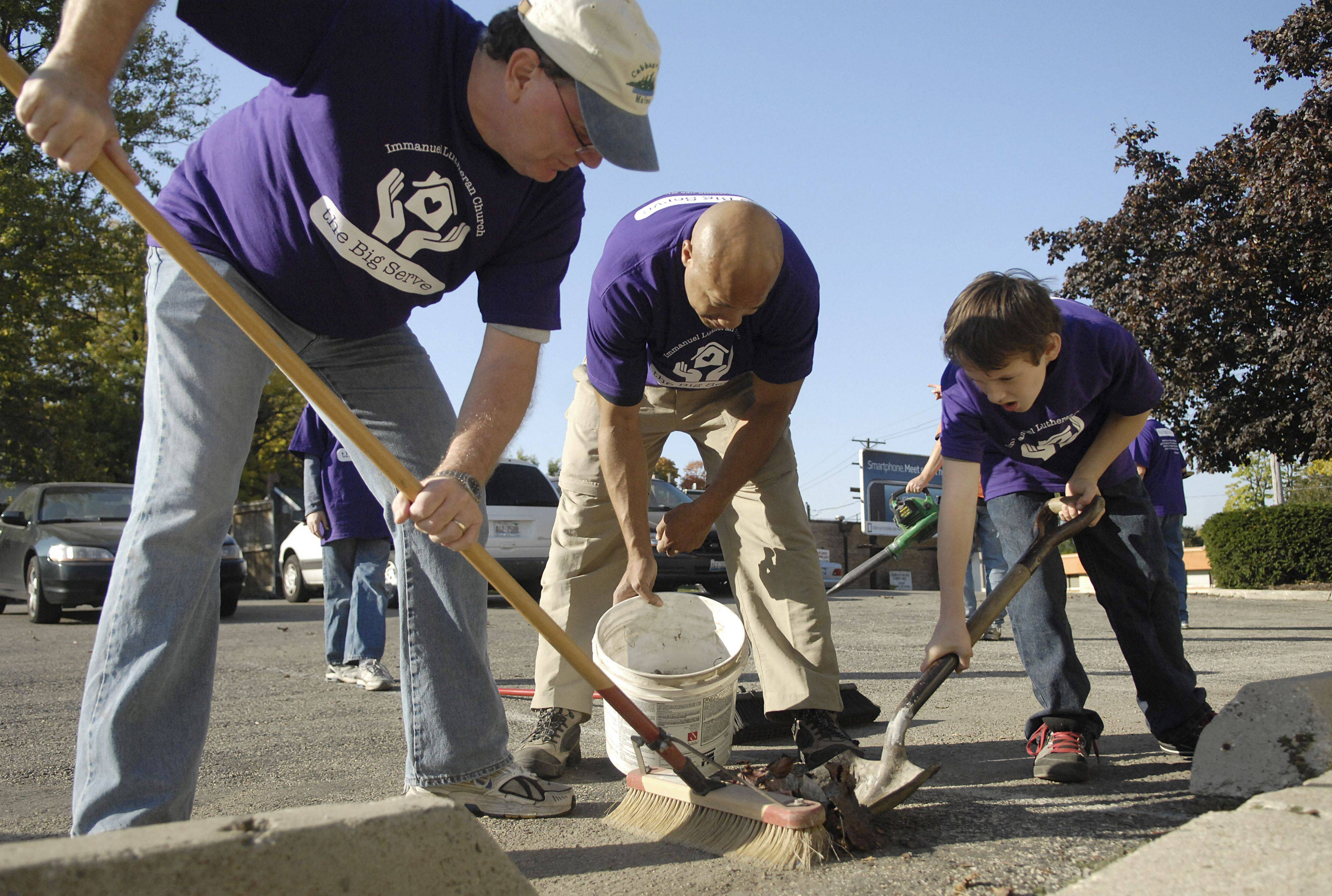 Joe Smedinghoff of West Dundee, Melvin Faulkner of Huntley and Austin Minella, 11, of Carpentersville use teamwork to sweep up debris from the parking lot of the Life Choices Pregnancy Center in Elgin. The men, from Immanuel Lutheran Church in East Dundee, were a part of dozens of volunteers who were spread throughout Elgin and neighboring towns during the congregation's The Big Serve day on Saturday, October 9.