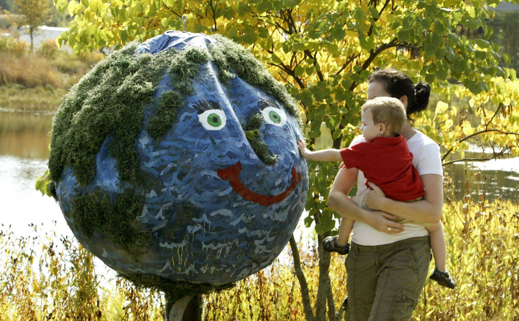 Jen Clark and her son Nathan, 2, of Chicago play with Mother Earth by Troop #50223 in Lombard during Scarecrows decorated by area Girl Scouts around Meadow Lake at the Morton Arboretum Sunday in Lisle.