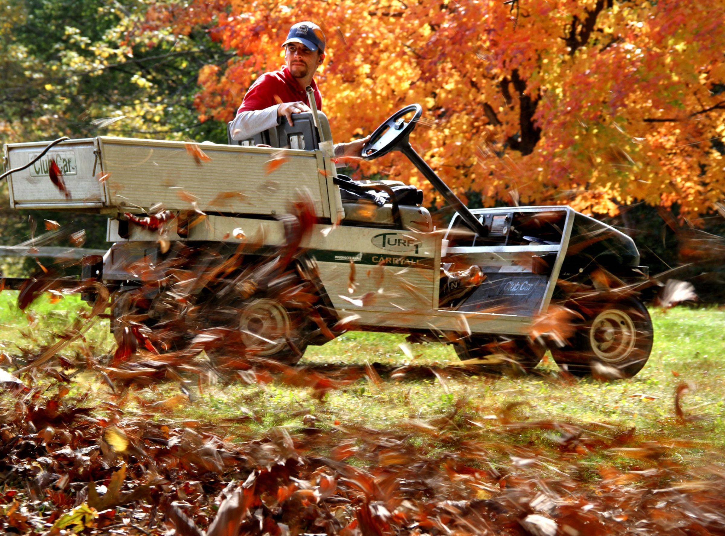 Jason McIntyre, golf course superintendent at Highland Woods Forest Preserve drives a golf cart pulling a large leaf blower near the parking lot of the course in Hoffman Estates on Tuesday, October 12.