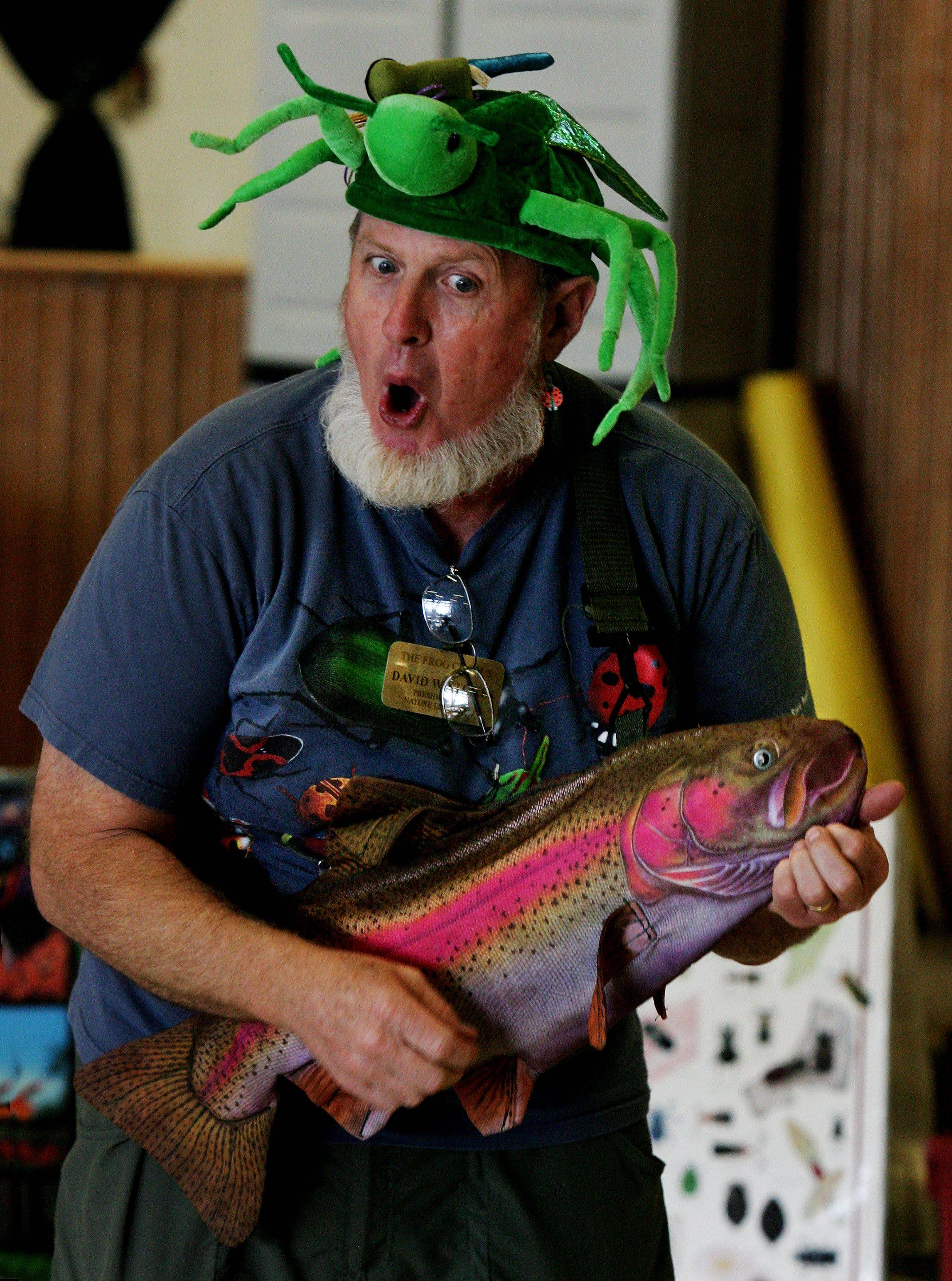 Naturalist David Stokes plays a trout guitar and wears a grasshopper hat while entertaining kindergarten students and teaching them about bugs and insects Tuesday at Woodland Primary School in Gurnee.