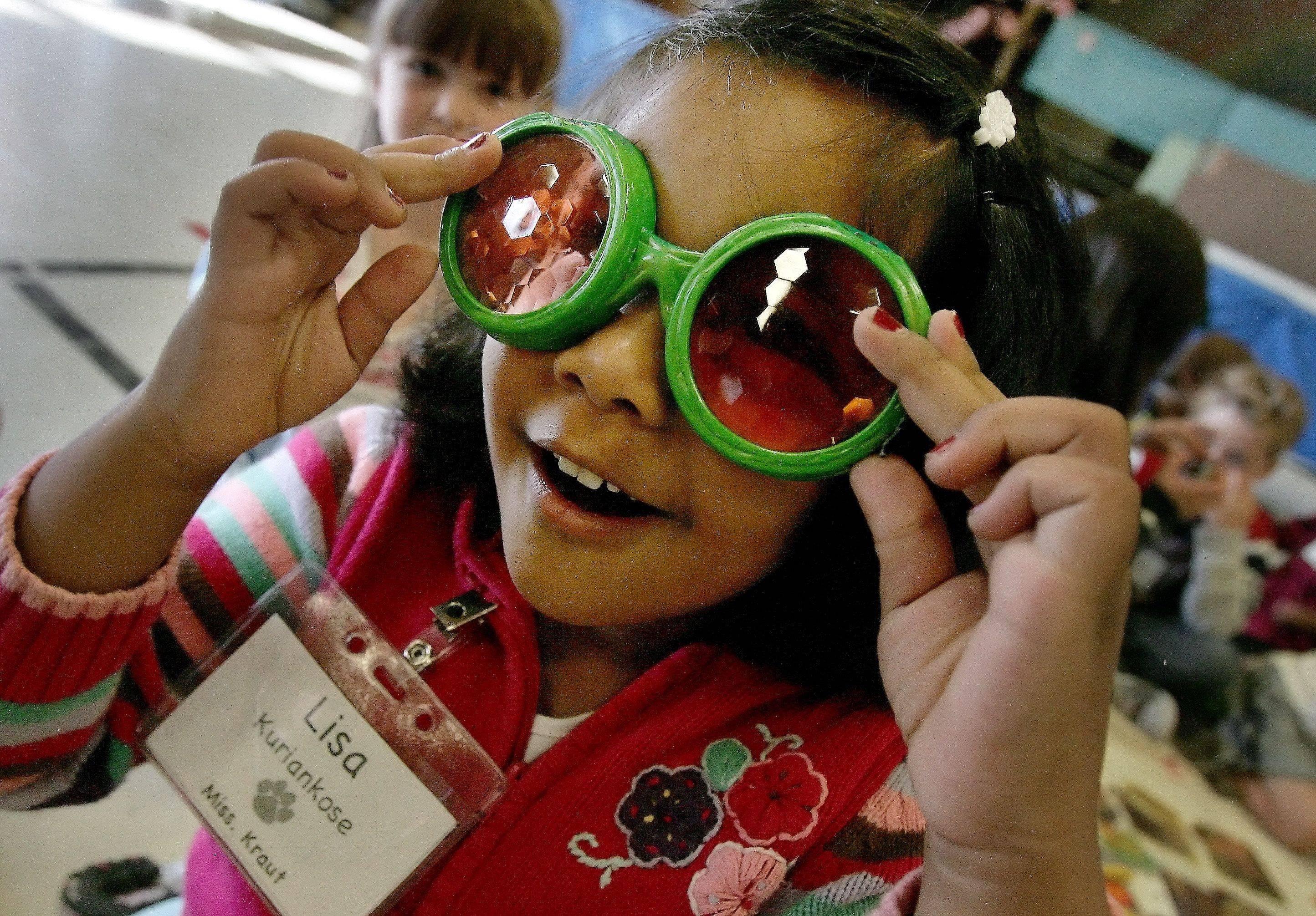 Lisa Kuriankose wears compound insect eye glasses as naturalist David Stokes talks to kindergarten students about bugs and insects Tuesday at Woodland Primary School in Gurnee.