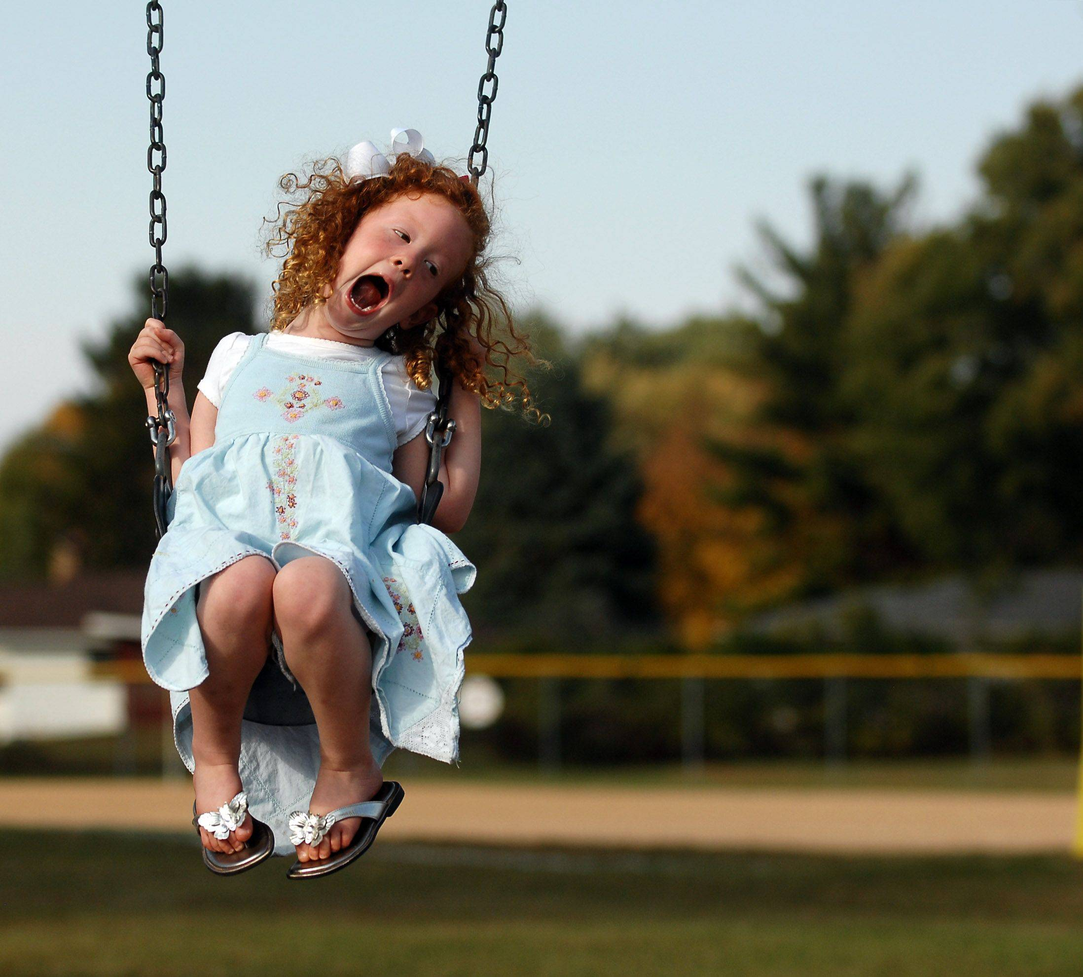 Three-year-old Henrietta Schultz of Batavia makes faces for her mom Sarah as she swings at Memorial Park in Batavia Monday. She and her older brothers and younger sister were enjoying the unseasonably warm temperatures.