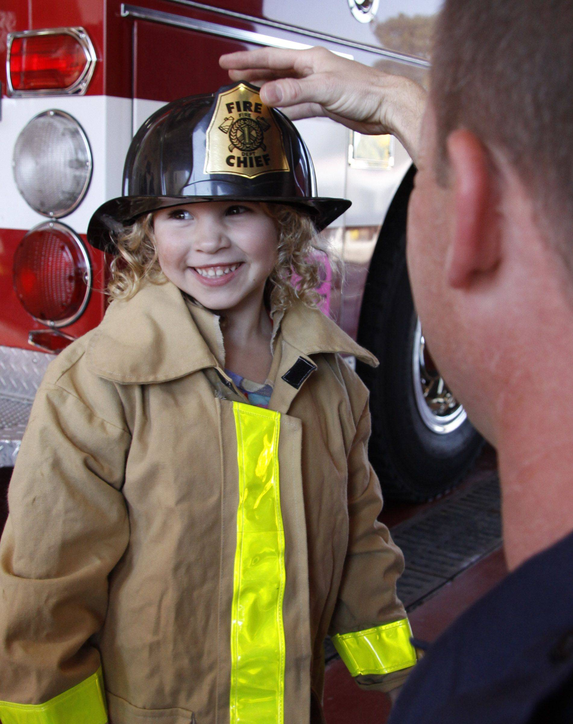 Sophia Opila, 4, of Lombard, tries on the firefighter's gear made smaller for the children at the Villa Park Fire Department's open house on fire safety Saturday in Villa Park.
