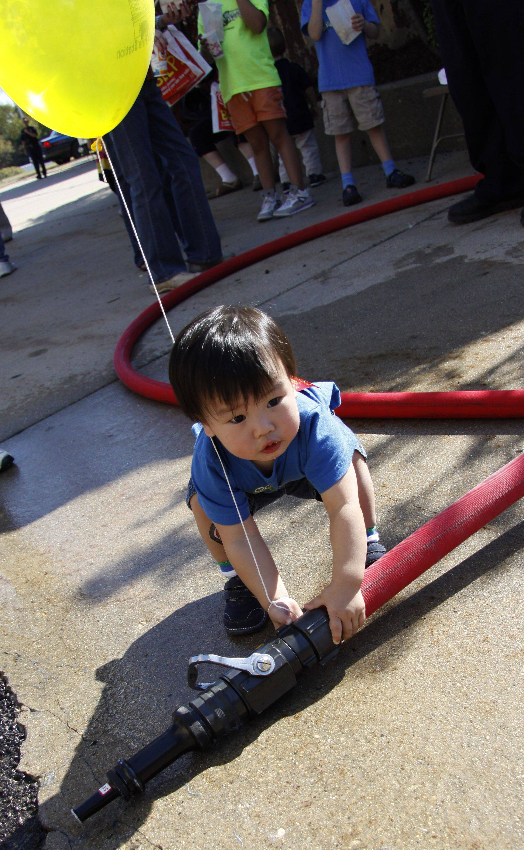 Cole Williams, 1 of Lombard, tries to pick up the fire hose when no one was looking at the Villa Park Fire Department's open house on fire safety held Saturday in Villa Park.