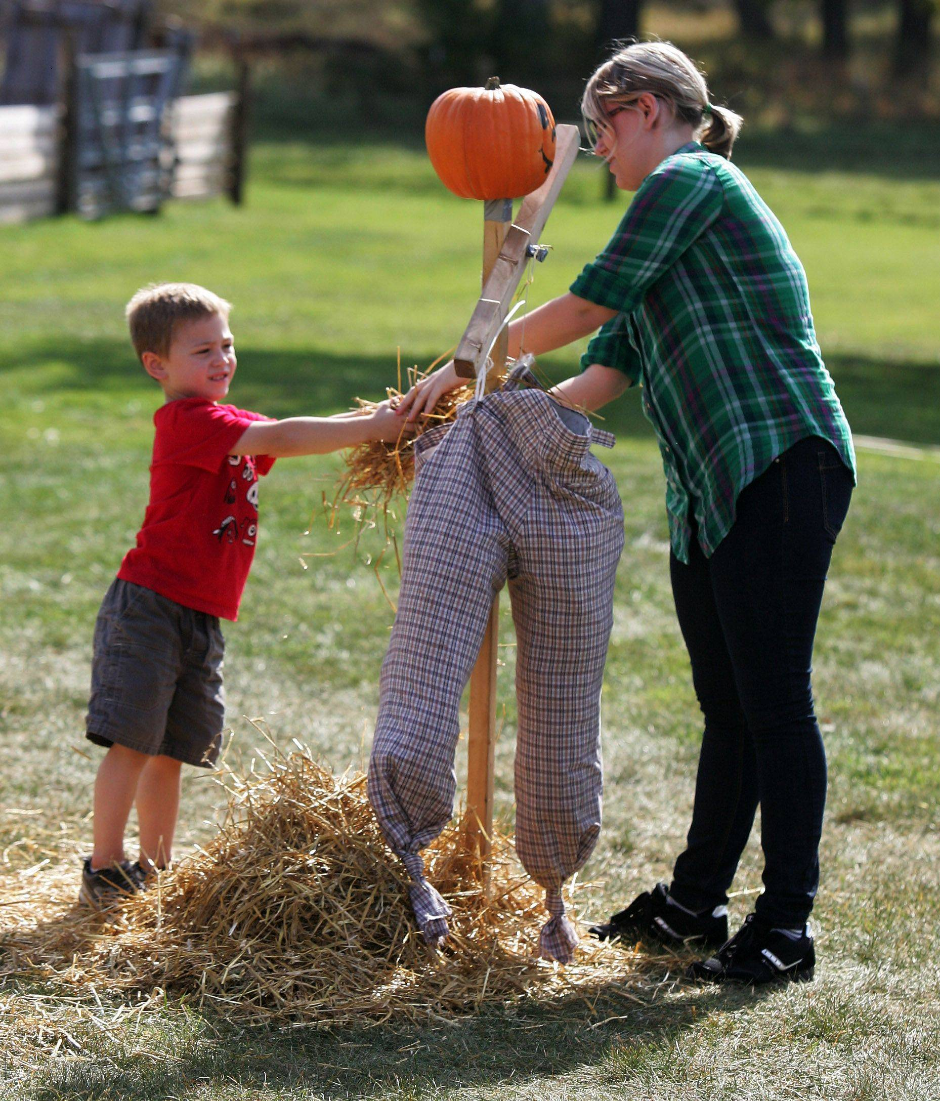 Carol Barbahen, right, and Donovan Wasilevich, both of Forest Park, stuff straw into a scarecrow during the Lake County Forest Preserve Fall Festival Sunday at Ryerson Woods in Riverwoods.