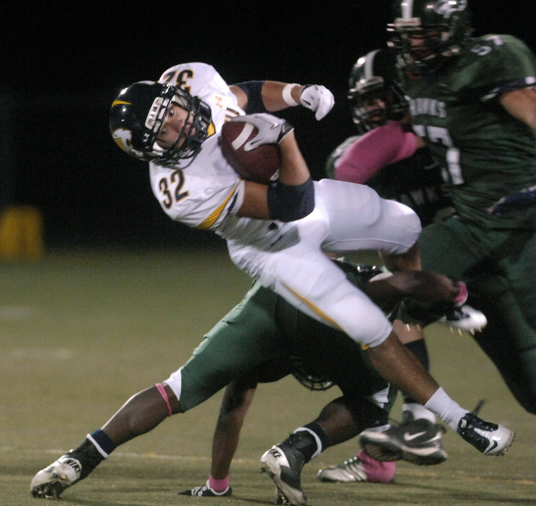 Neuqua Valley's Vai Suliafu is tripped up by a Bartlett tackler during Friday's game at Millennium Field in Streamwood.