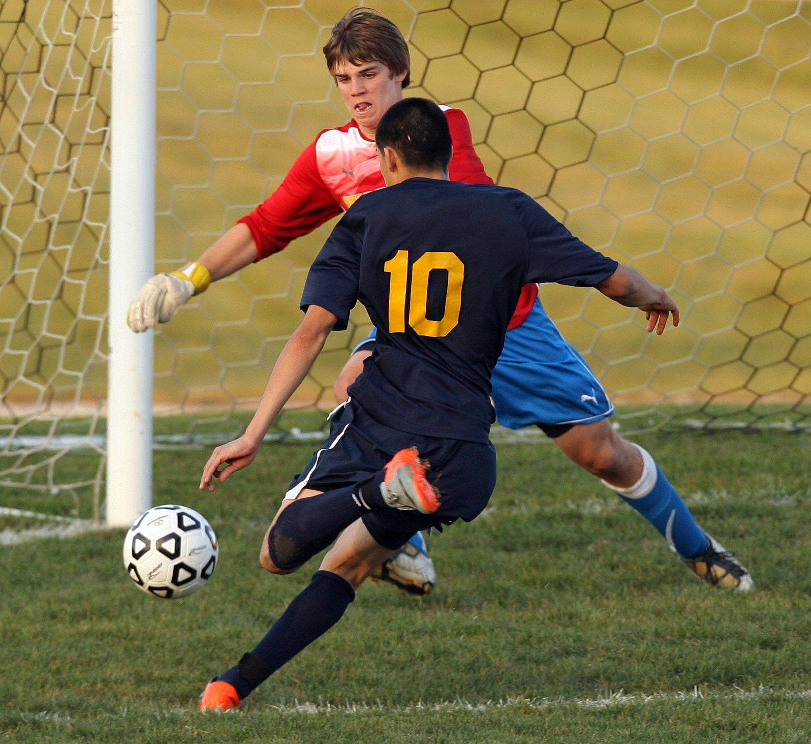 Round Lake's Emanuel Salgado drives on Warren goal keeper Brady Walsh during the NSC title game against Tuesday at Warren High School.