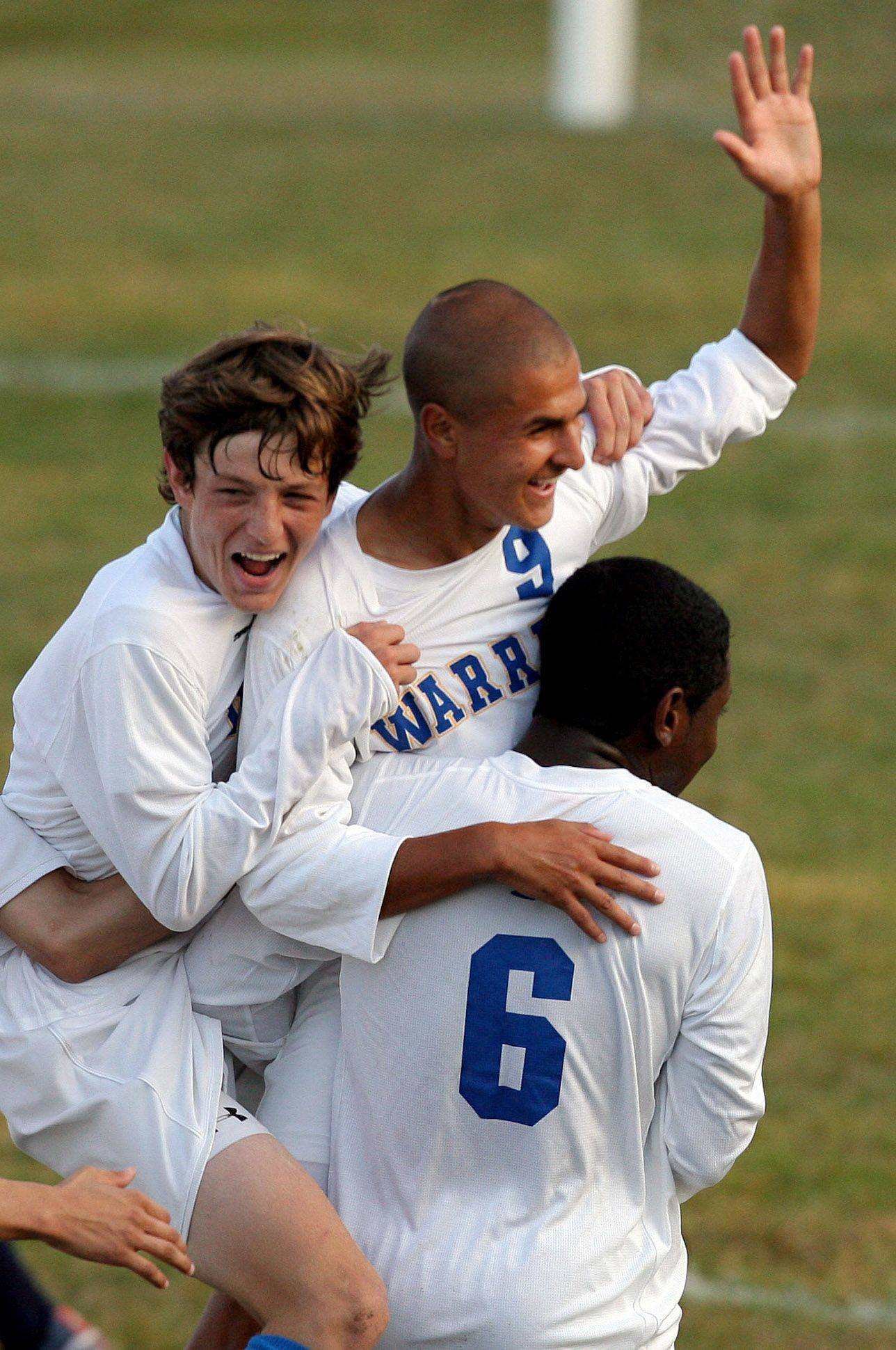 Warren's Daniel Szczepanek, middle, is mobbed by teammates Alex Buvala, left and Leon Mardehow after Szczepanek's second goal of the game during the NSC title game against Round Lake Tuesday at Warren High School.
