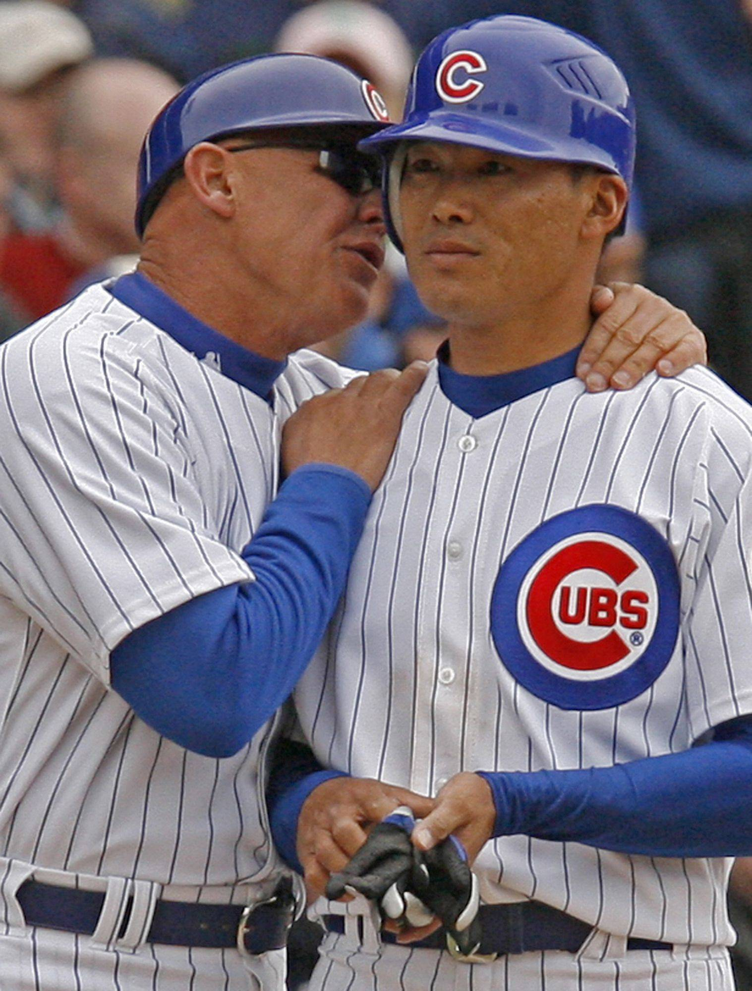Chicago Cubs third base coach Mike Quade, left, talks to player Kosuke Fukudome of Japan, during the fourth inning of a baseball game against Milwaukee Brewers.