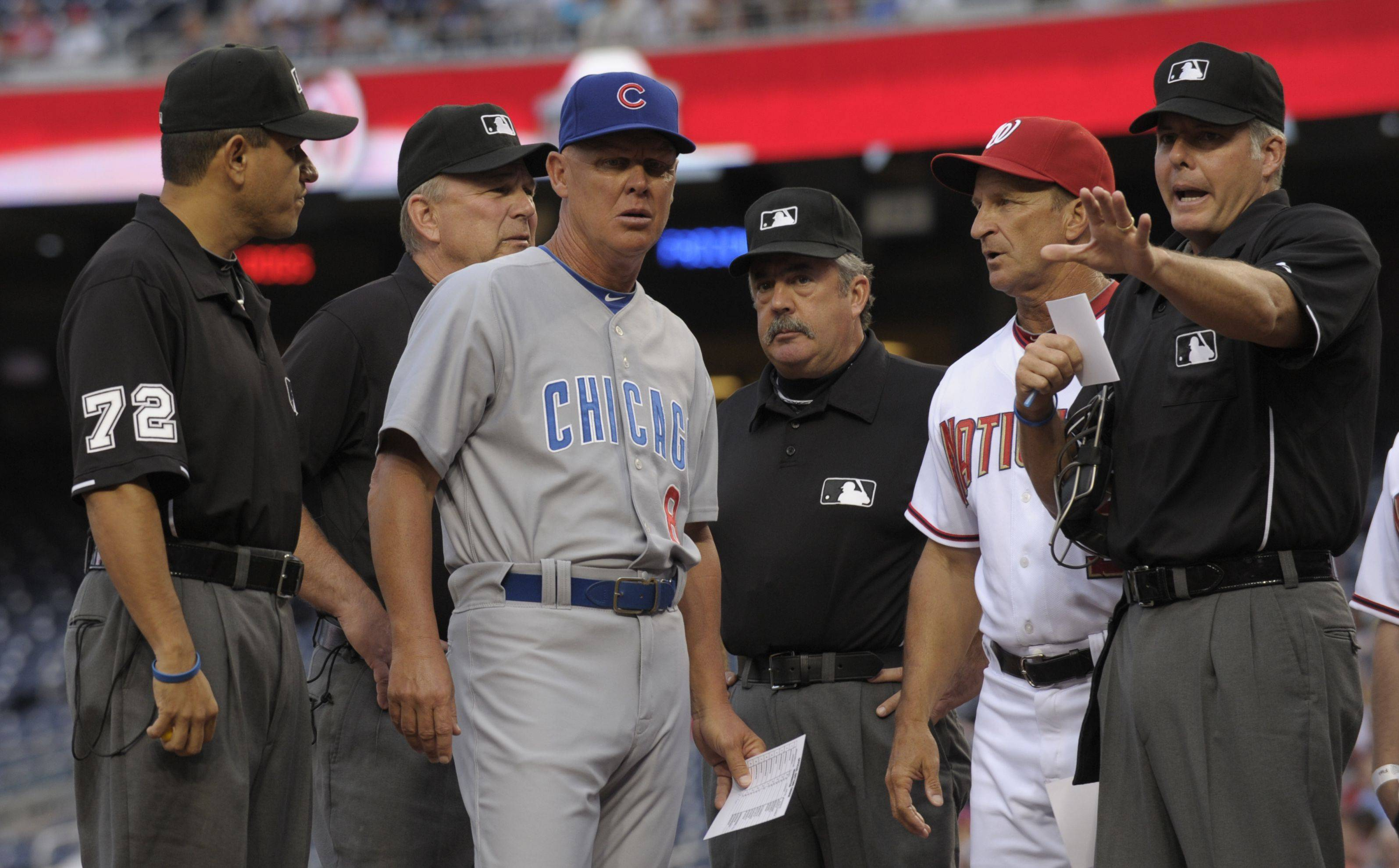 Chicago Cubs manager Mike Quade, third from left, and Washington Nationals manager Jim Riggleman, second from right, talk with the umpires before the start of their game at Nationals Park in Washington.
