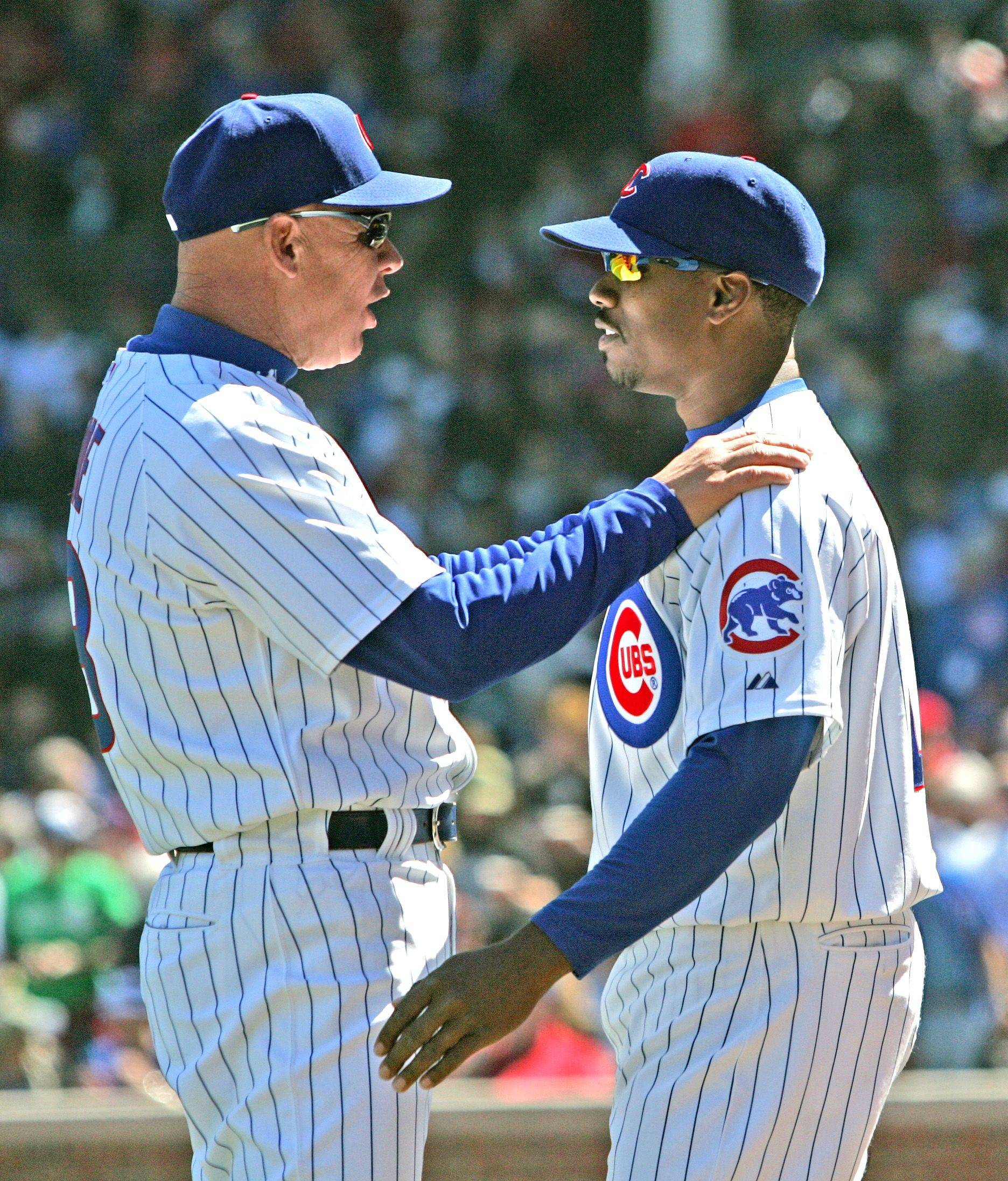 Chicago Cub third base coach Mike Quade talks to third baseman Aramis Ramirez during a game with the St. Louis Cardinals.
