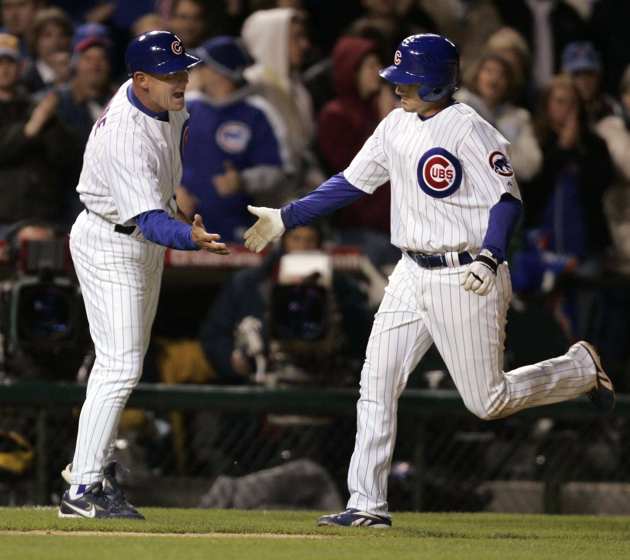 Cubs third base coach Mike Quade slaps hands with Ryan Theriot as he rounds third after his two run home run in the 8th inning.