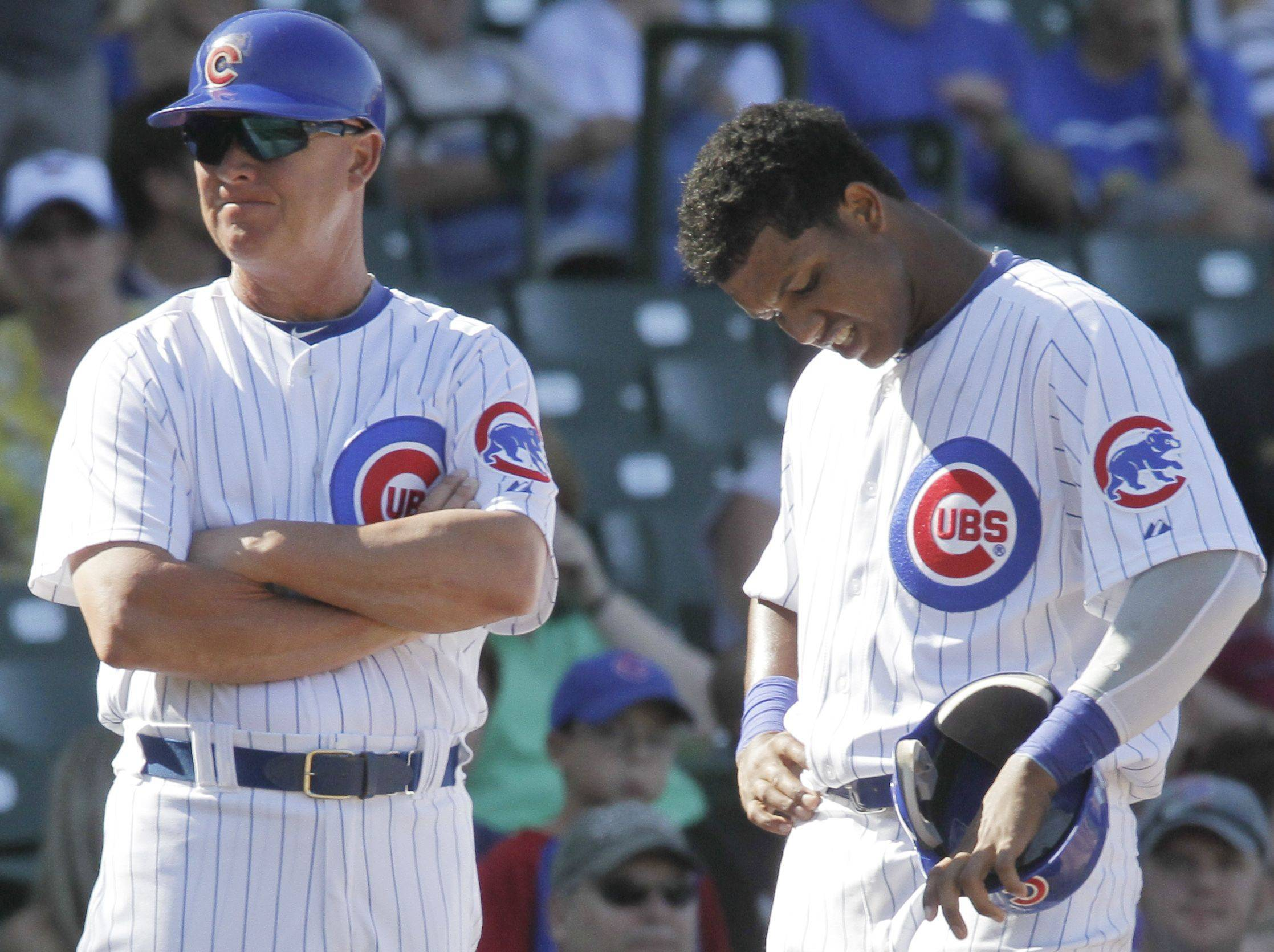 Chicago Cubs third base coach Mike Quade, left, and Starlin Castro react as their team plays against the Atlanta Braves during the ninth inning of a baseball game.