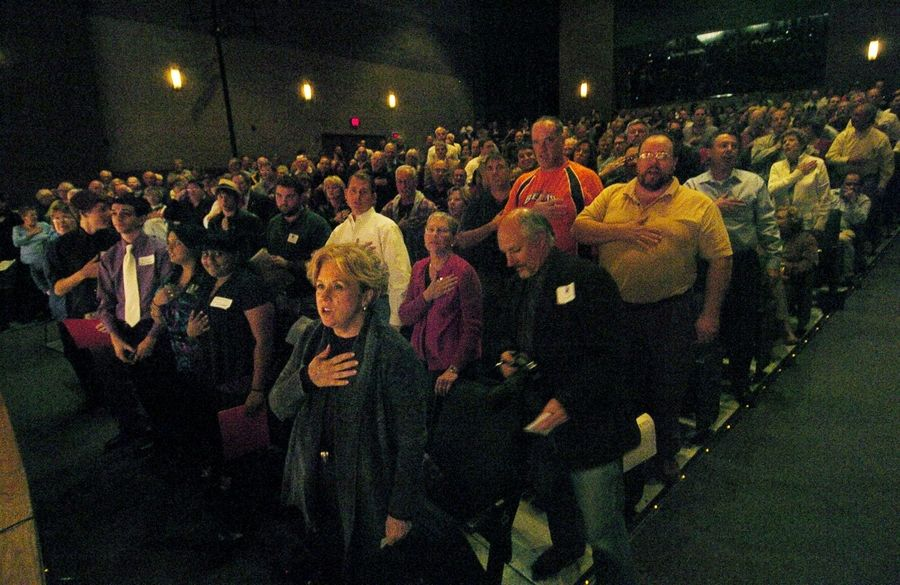 The crowd breaks into an impromptu Pledge of Allegiance at the beginning of the candidates forum between 8th Congressional District candidates Joe Walsh, Melissa Bean and Bill Scheurer at Grayslake Central High School.