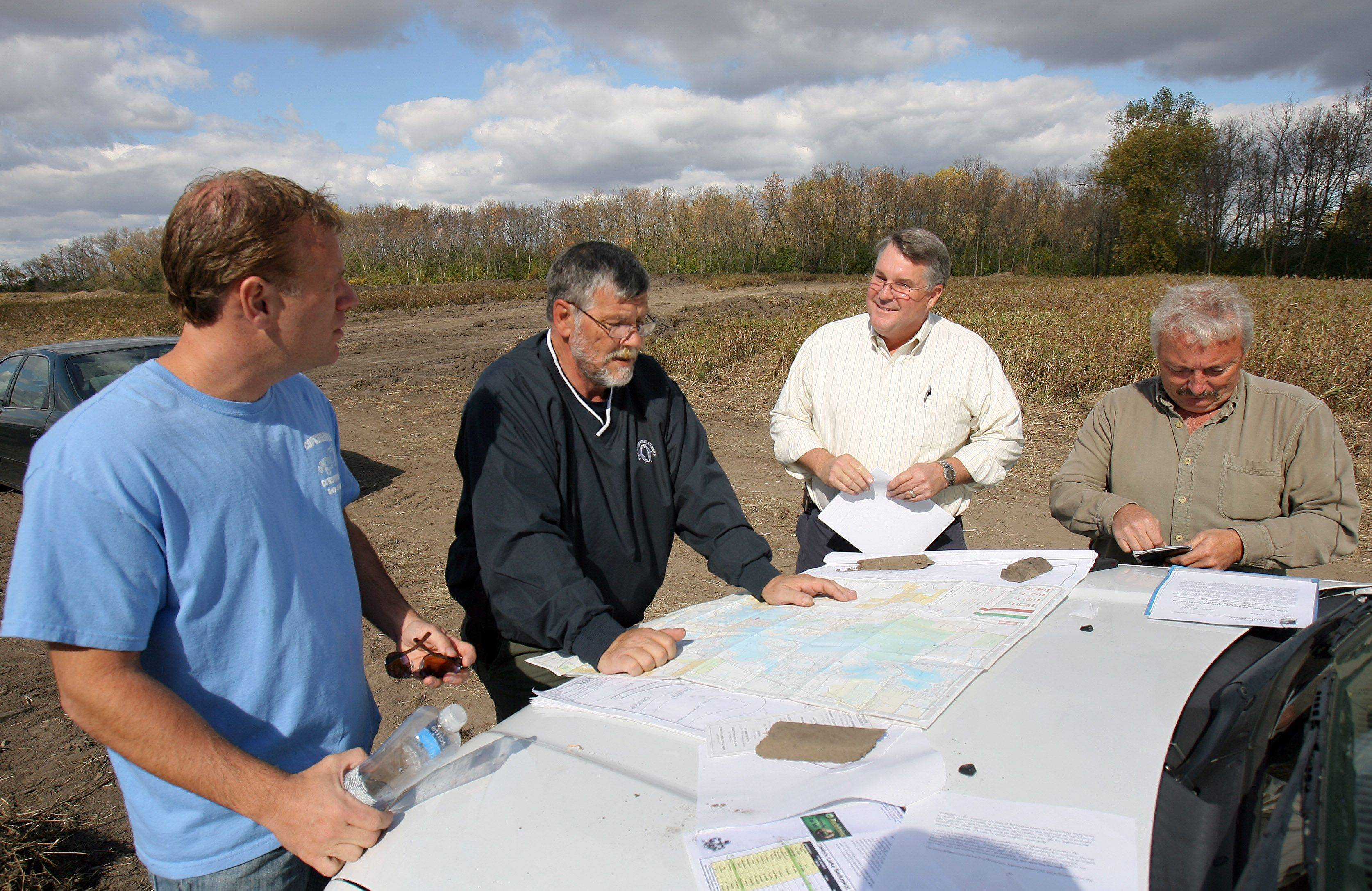 Ken Copenhaver, president of Copenhaver Construction; Ron Barker, deputy director of the Fox Waterway Agency; Jim Meyer, director of the Fox Waterway Agency; and, Wayne Blake, chairman of the Fox Waterway Agency, from left, check plans Friday for Cooper Farms. The $880,000 project that greatly increase the area in which the agency can store and dry sediment dredged from area waterways.