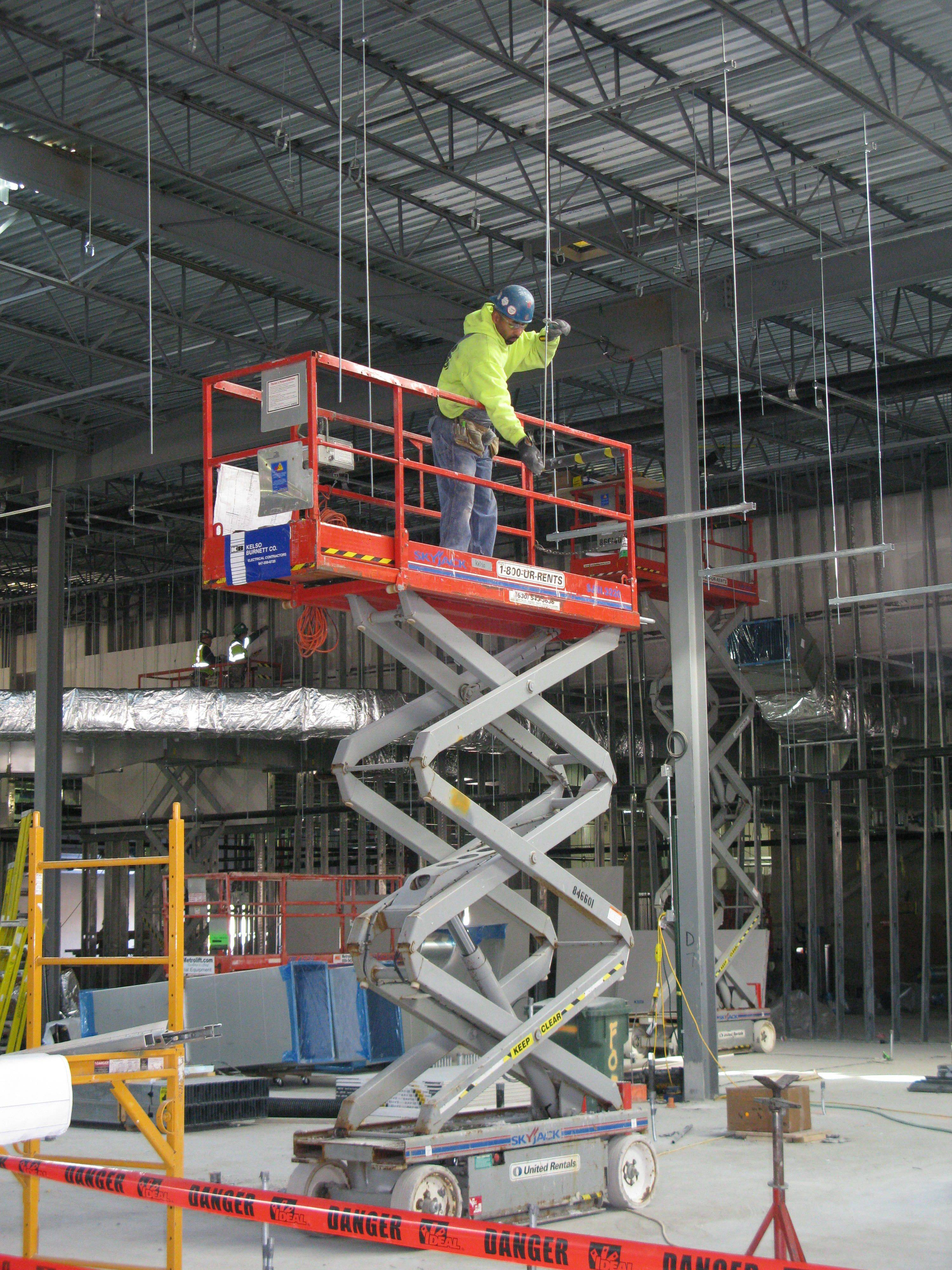 A construction worker installs hangers for overhead ducts Thursday at the Des Plaines casino site.