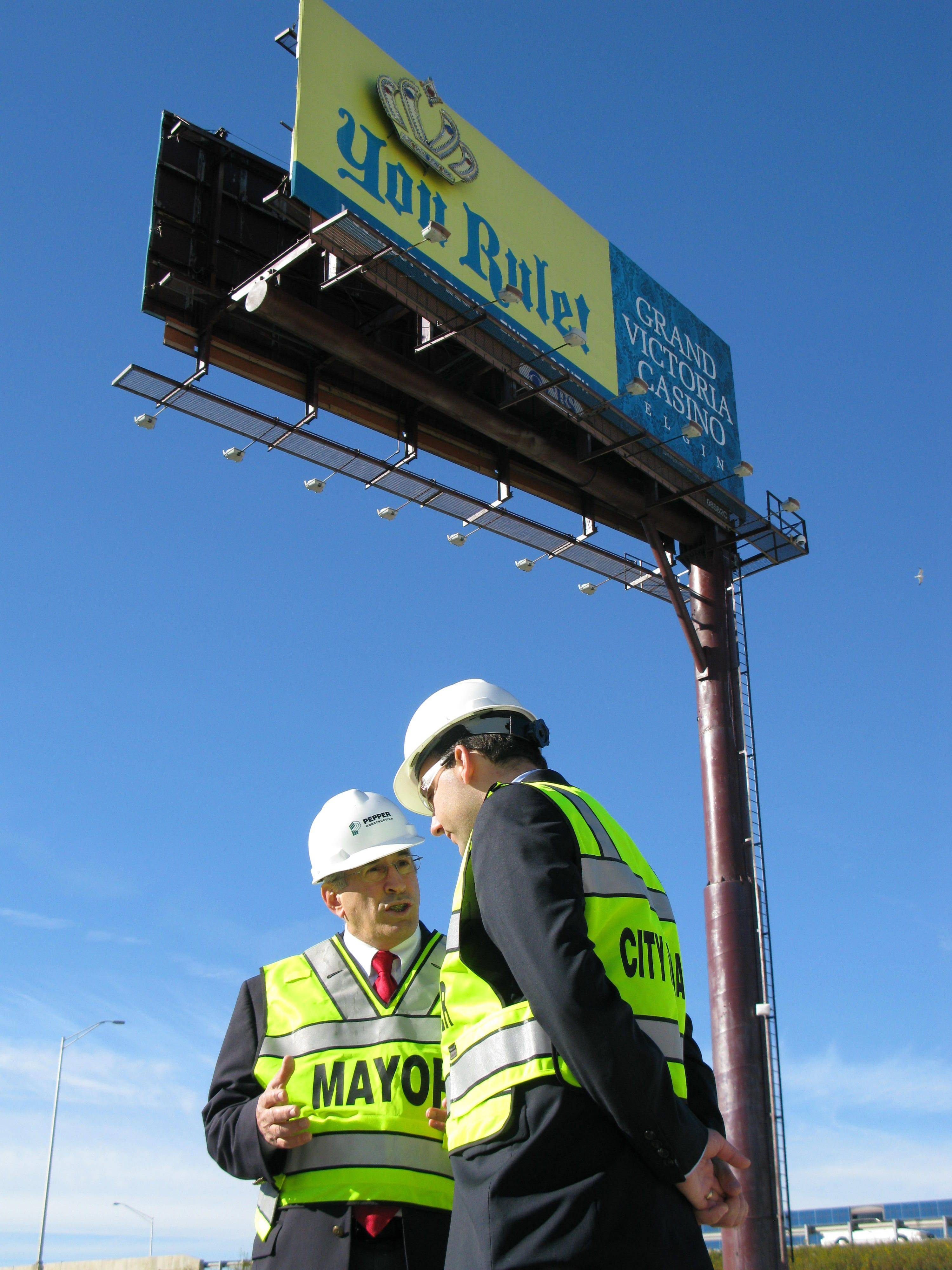A billboard promoting Elgin's Grand Victoria Casino looms over the site of Des Plaines' casino. Mayor Marty Moylan, left, and acting City Manager Jason Slowinski said the billboard has been there for a long time, but Slowinski expects it to come down before Des Plaines' casino opens in late summer 2011.