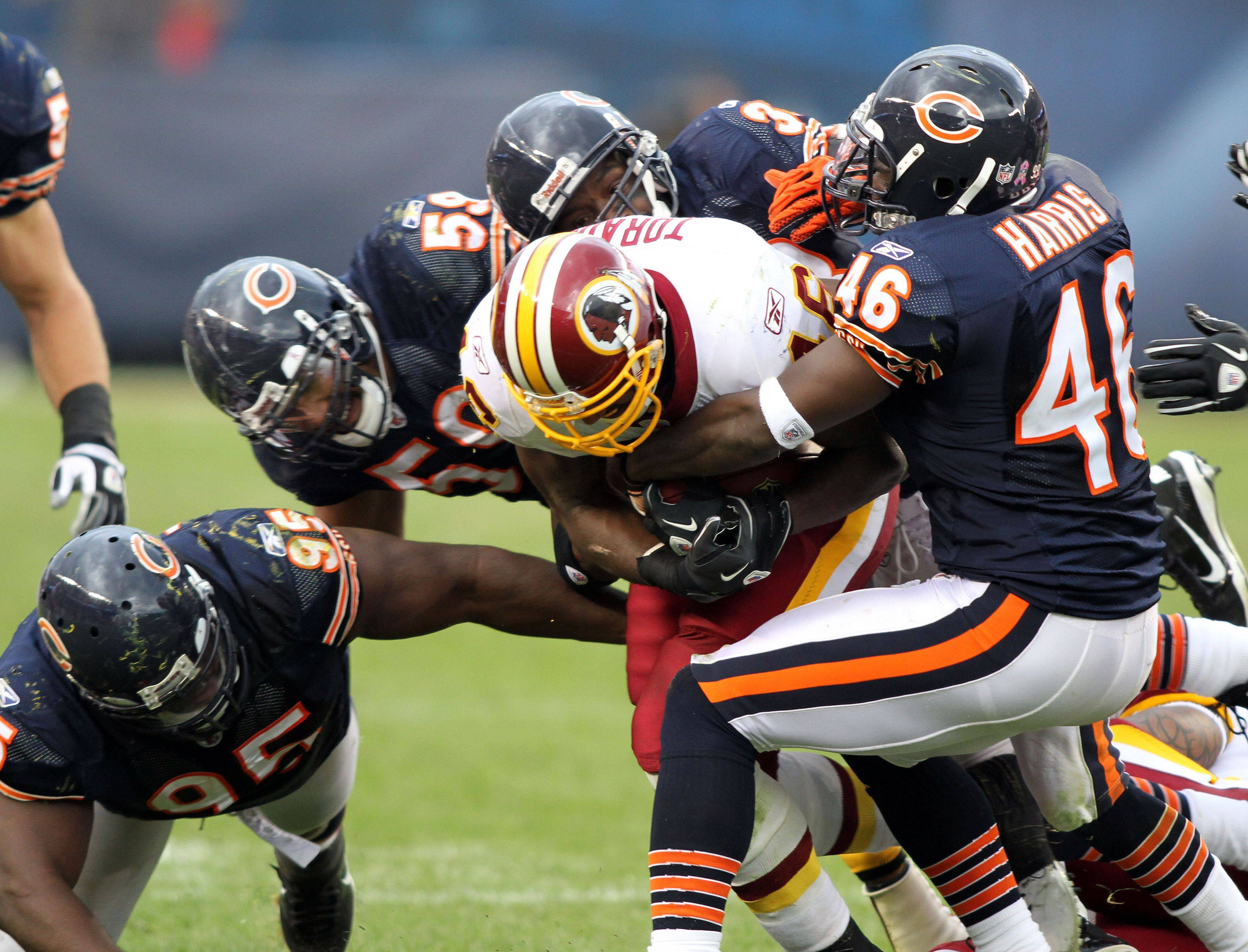 A throng of Bears take down Washington Redskins running back Ryan Torain during the Bears' 14-17 loss to the Redskins Sunday at Soldier Field in Chicago.