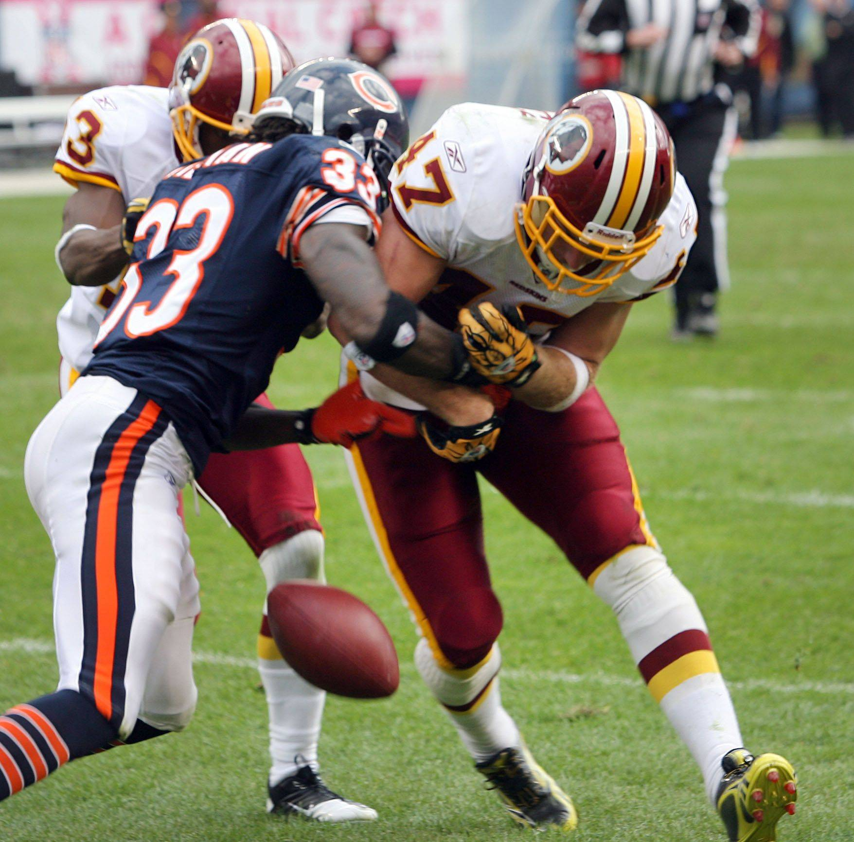 Chicago Bears cornerback Charles Tillman forces a fumble from Washington Redskins tight end Chris Cooley during the Bears' 14-17 loss to the Redskins.