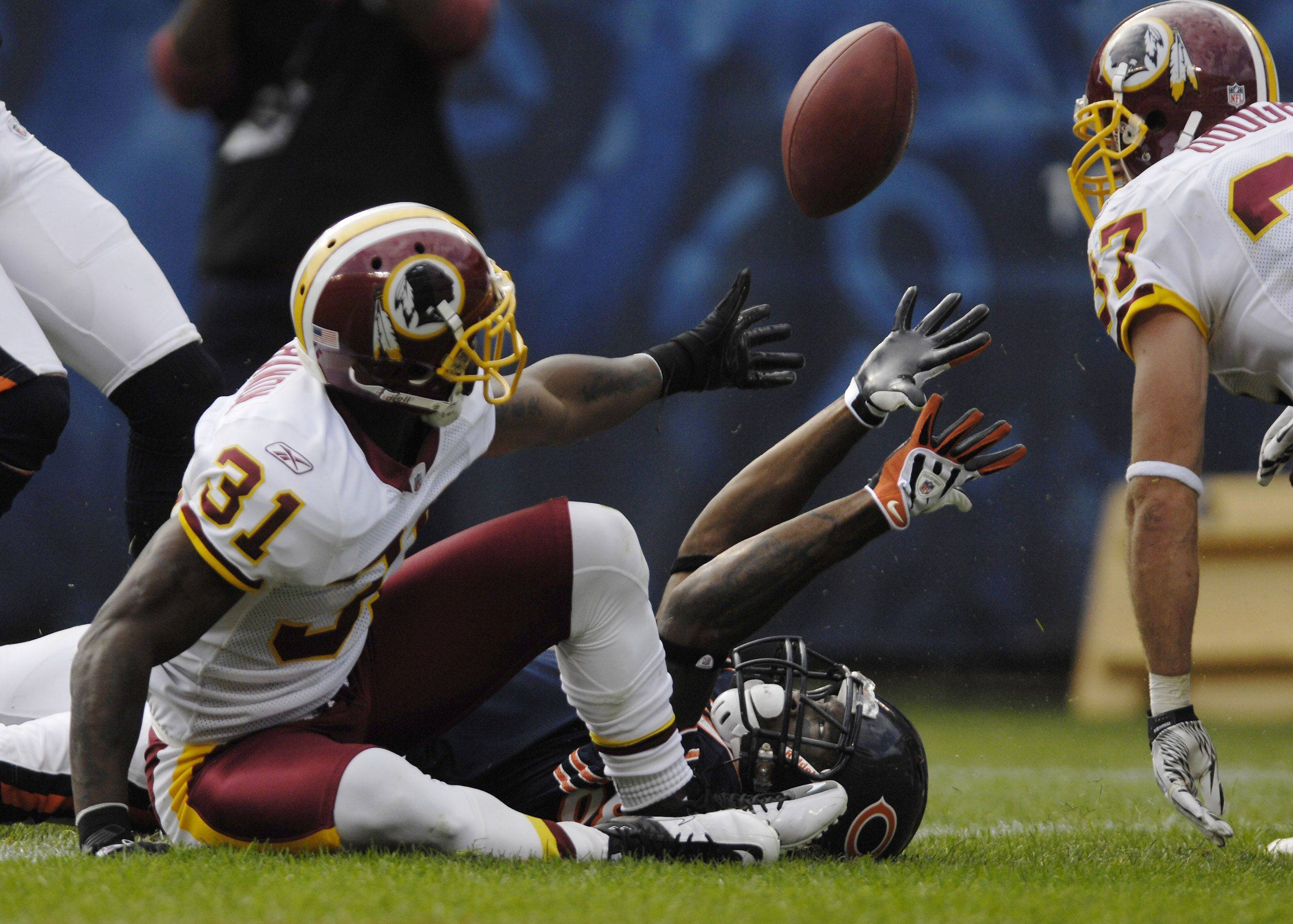Chicago Bears wide receiver Earl Bennett reaches for the ball after being stopped at the one-foot line by Washington Redskins cornerback Phillip Buchanon. He caught the ball and quarterback Jay Cutler fumbled the ball on the next play.