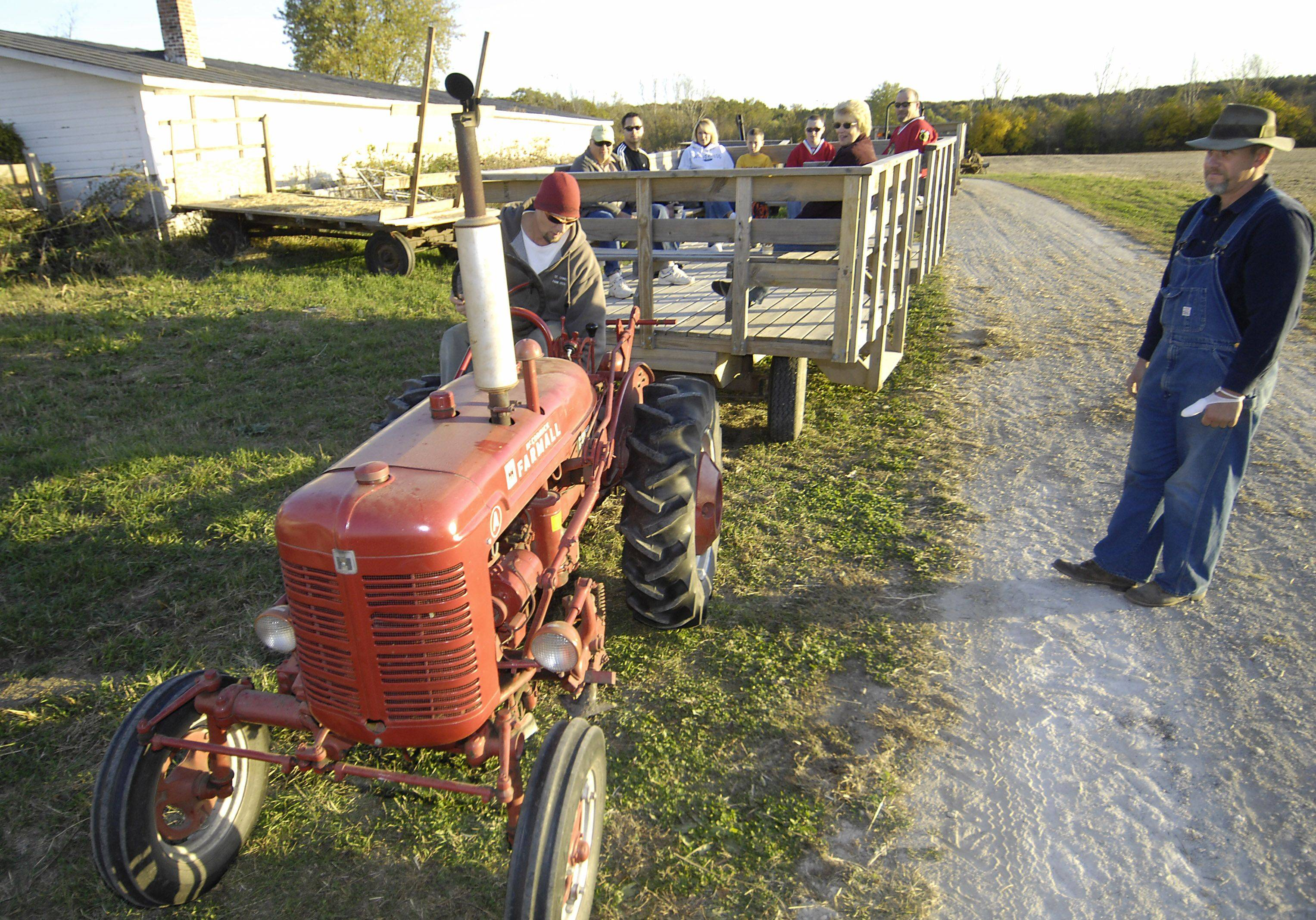 Paul Anderson starts a 1952A Farmall tractor Sunday evening for a hayride at Primrose Farm in St. Charles. He is a park district employee. At right is farm manager Kirk Bunke. The historic 150-year-old farm also provided hayrides with new tractors.