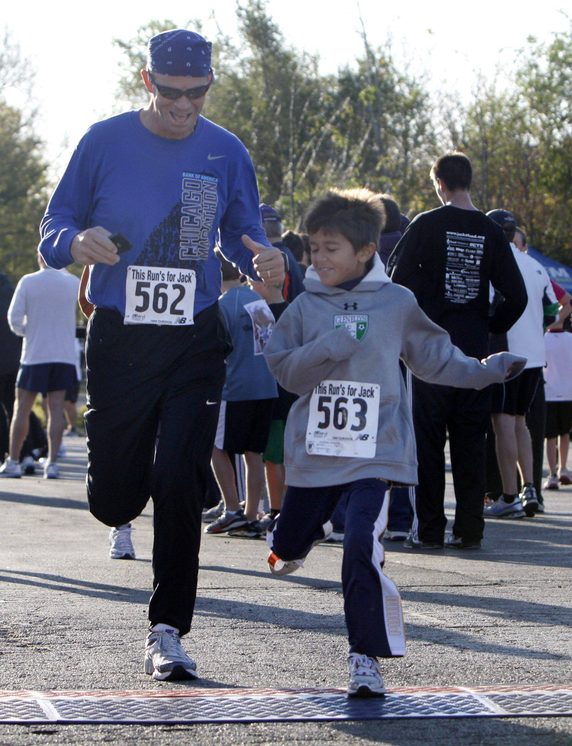 Karl Irwin of Glen Ellyn and his eight-year-old son Kyle stroll to the finish line at the seventh-annual This Run's for Jack 5K run/walk Sunday at Ackerman Park in Glen Ellyn.