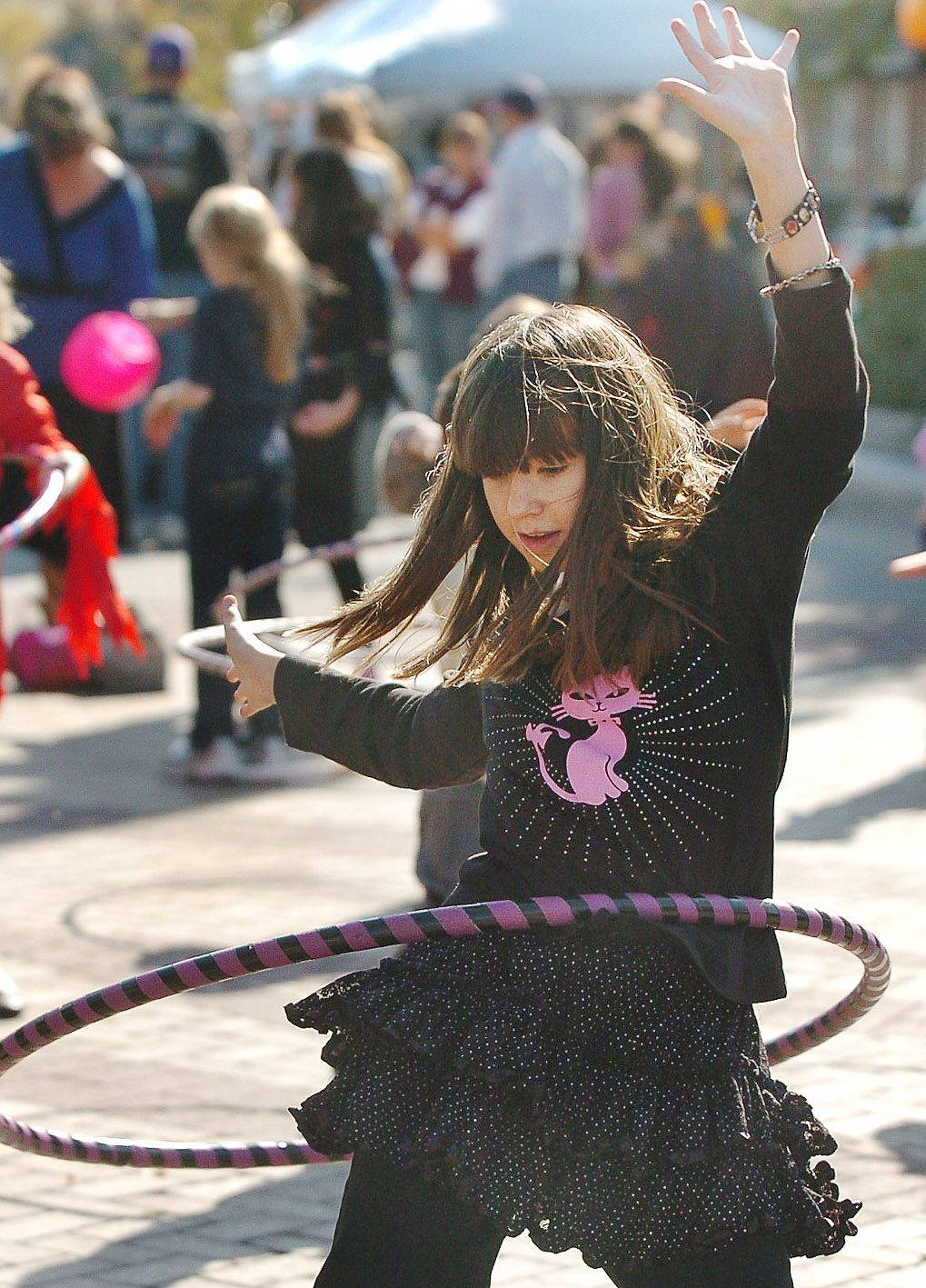 13-year-old Meghan Lecey tries her luck at hula hooping at Mount Prospect's sixth-annual Fall Festival.