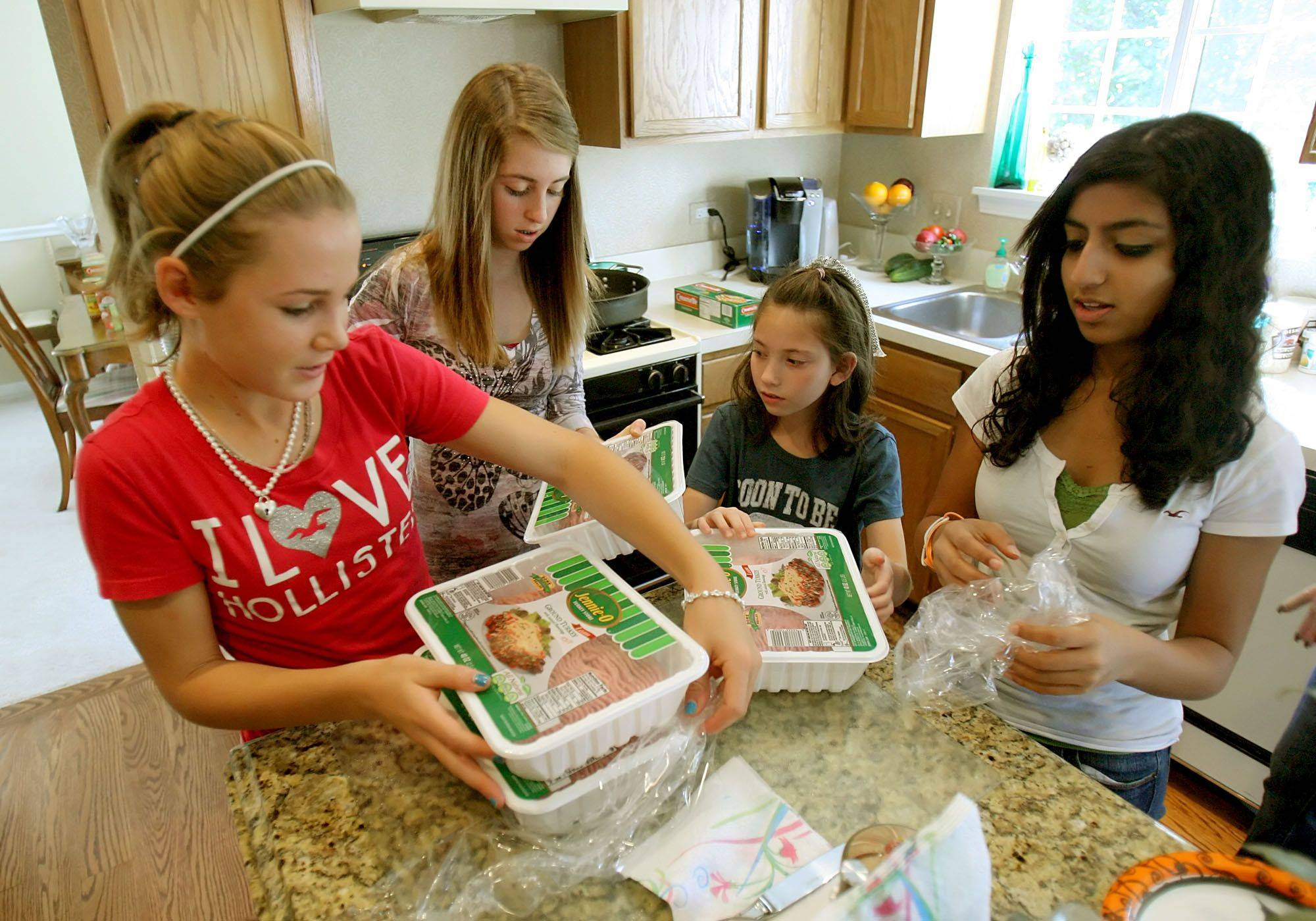 Alison Deluca, 13, left, Jessica Schwartz 13, Peyton Friedlander, 9, and Diya Verma, 13, all of Gurnee, prepare lasagna for the two Gurnee fire departments and one Gurnee police department for their charity called Cheers for Heros.