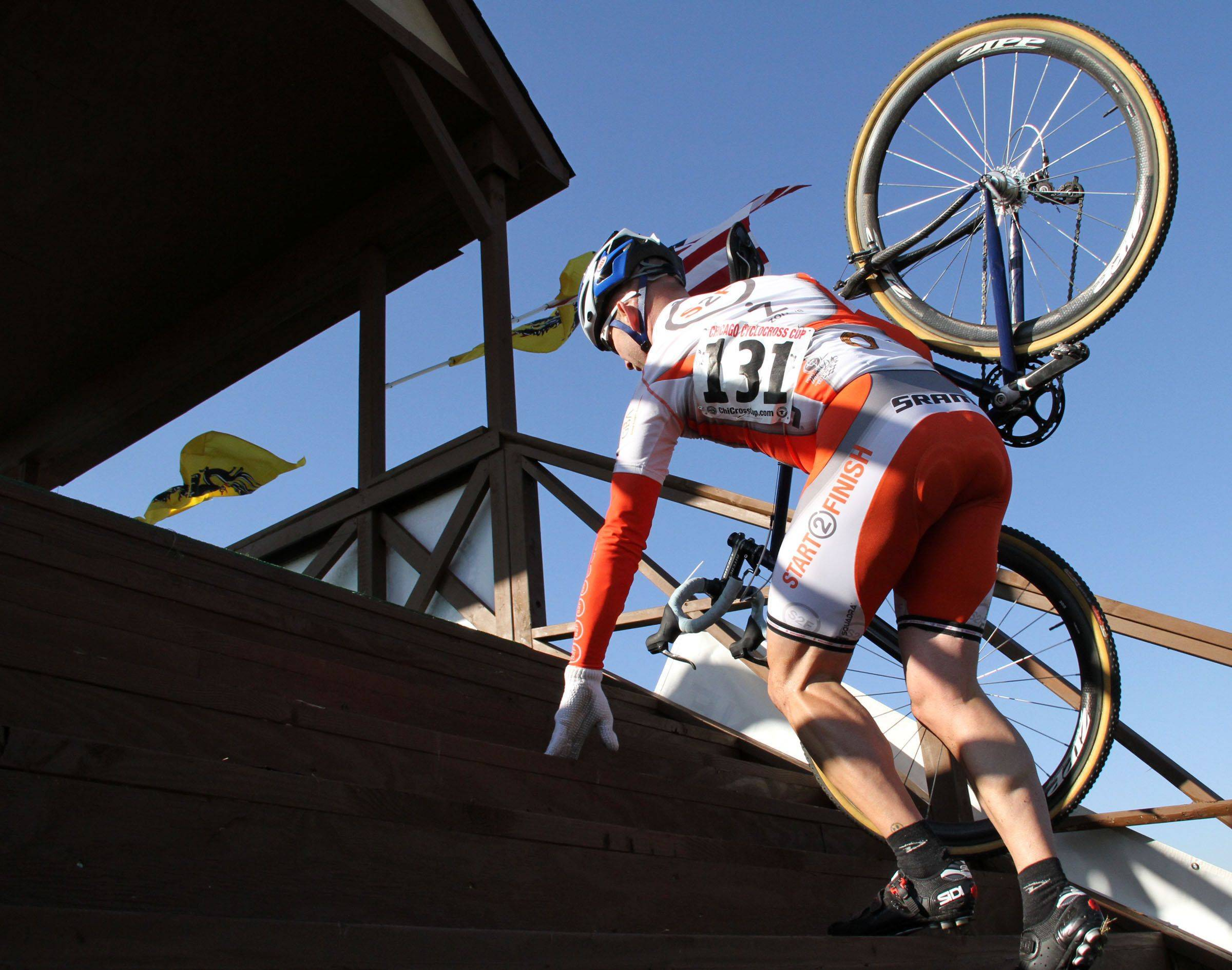 Peter Rolewicz of Chicago of the Start2Finish race team carries his bike up the fly-over bridge during the Masters 40+ race during the Chicago Cyclocross Cup Race at The Golf Farm in Wauconda on Saturday, October 16.