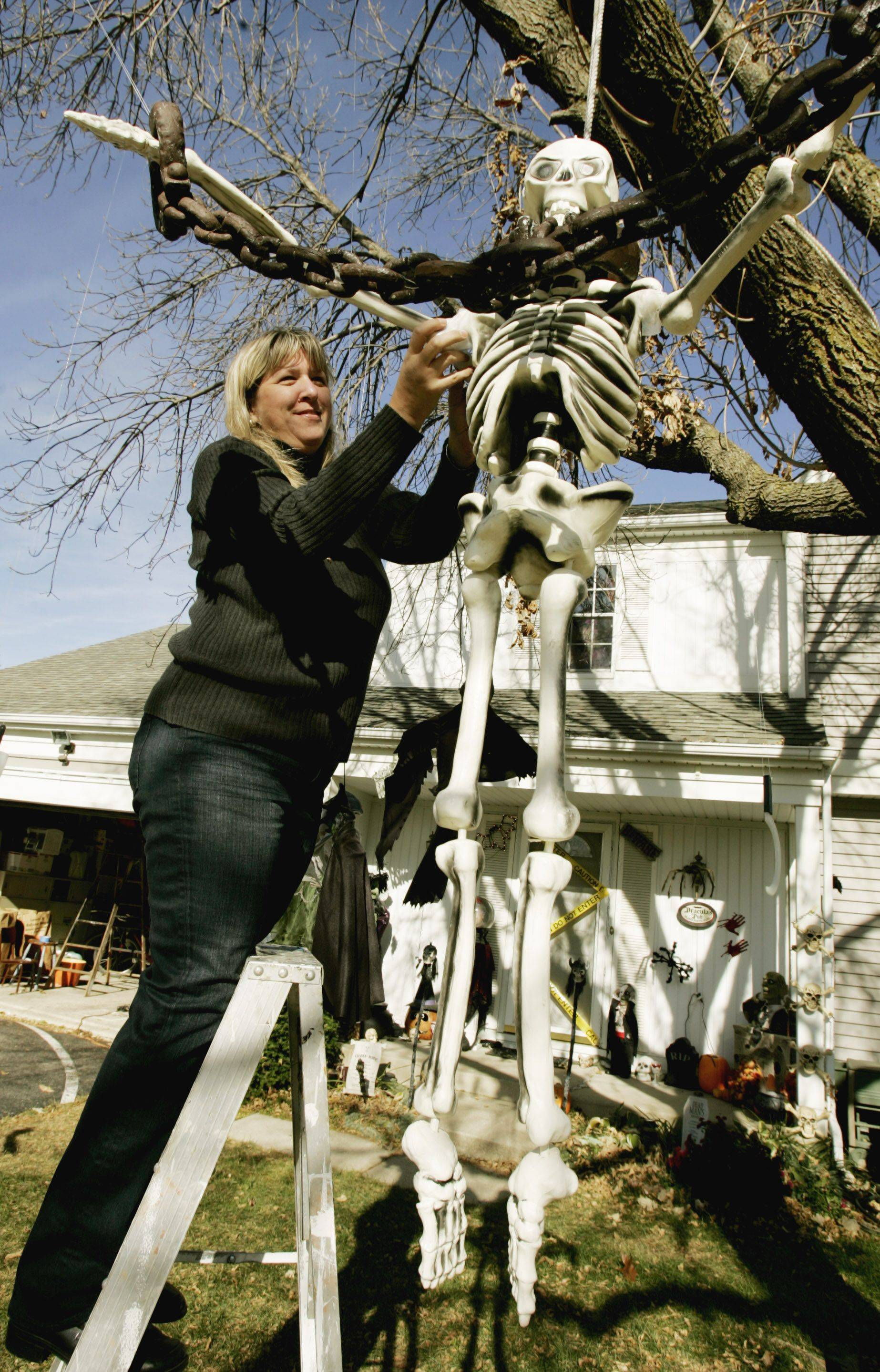 Karla Edmondson of Aurora gets her front yard ready for Halloween.