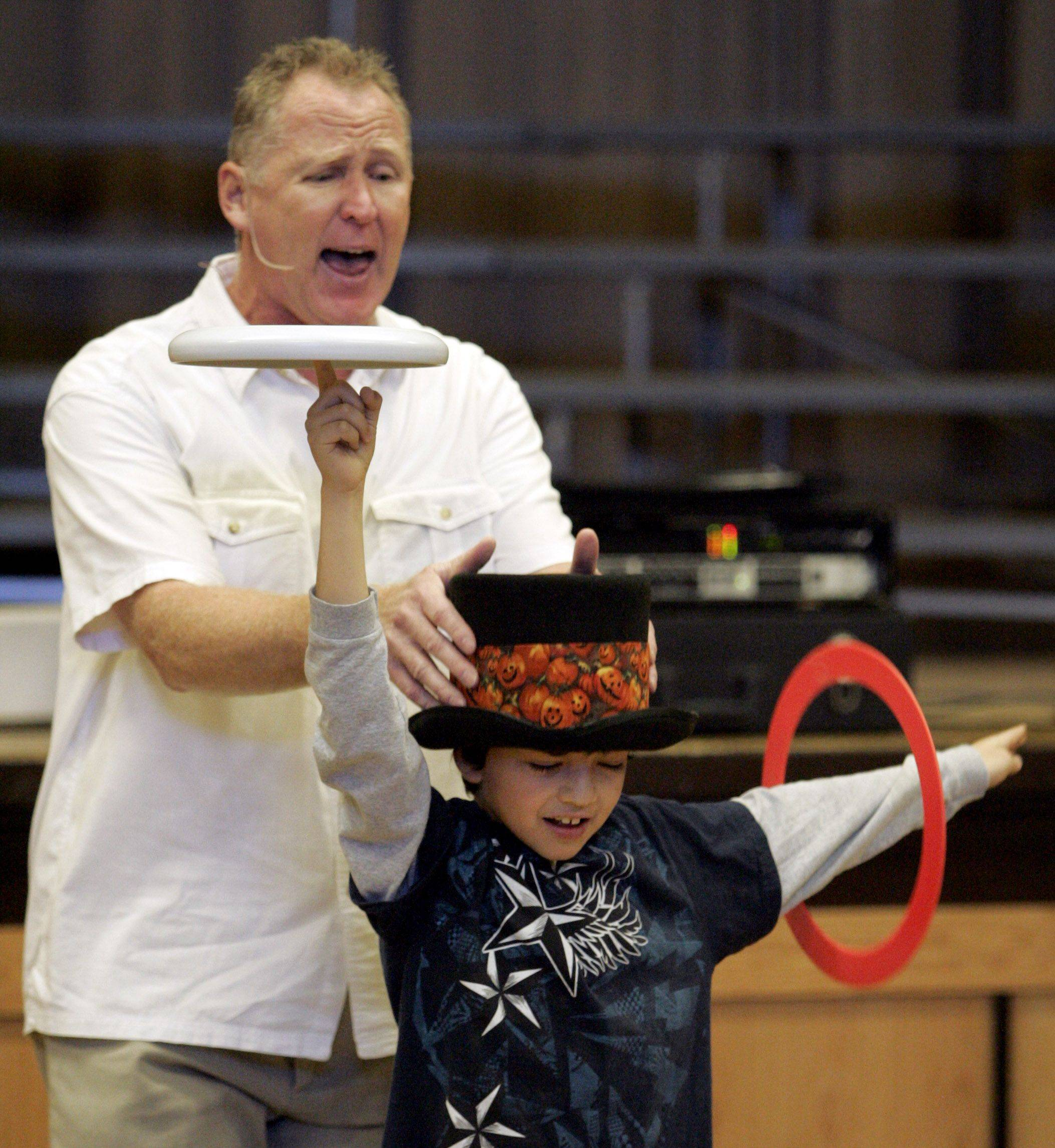 Third grader Gerardo Gil performs with juggling expert Mike Vondruska during an assembly at Diamond Lake School in Mundelein.