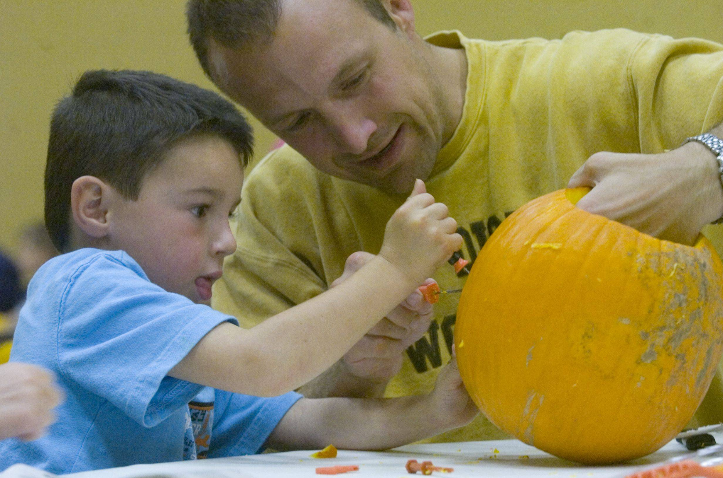 Five-year-old Sammy Wederich of St. Charles narrows in on his scary monster jack o' lantern with his dad, Bob Werderich, at Hosanna! Lutheren Church's 22nd-annual Dad Pumpkin Carving Night Thursday evening. The preschool students at Hosanna! went on a field trip to Goebbert's Farm last week to pick out their pumpkins for carving night.