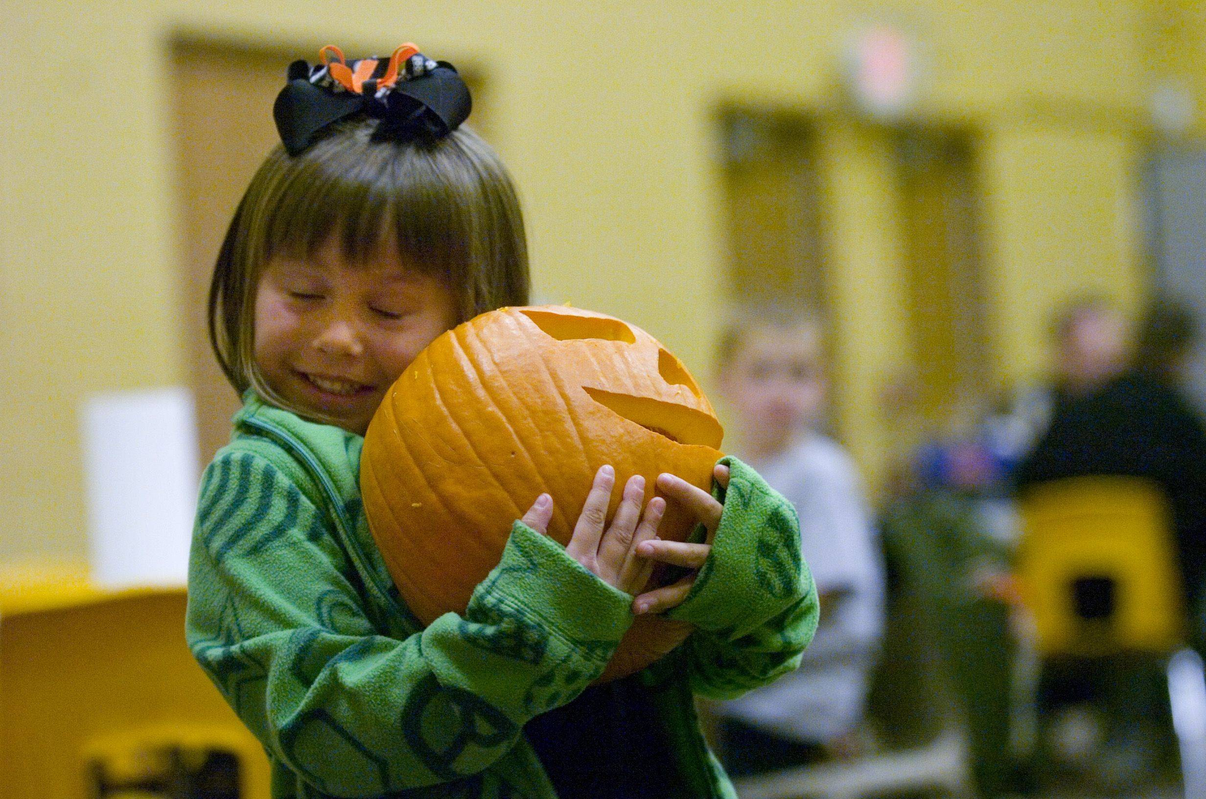 Claire Escaro, 4, from South Elgin hugs her jack o' lantern at Hosanna! Lutheren Church's 22nd annual Dad Pumpkin Carving Night Thursday evening.