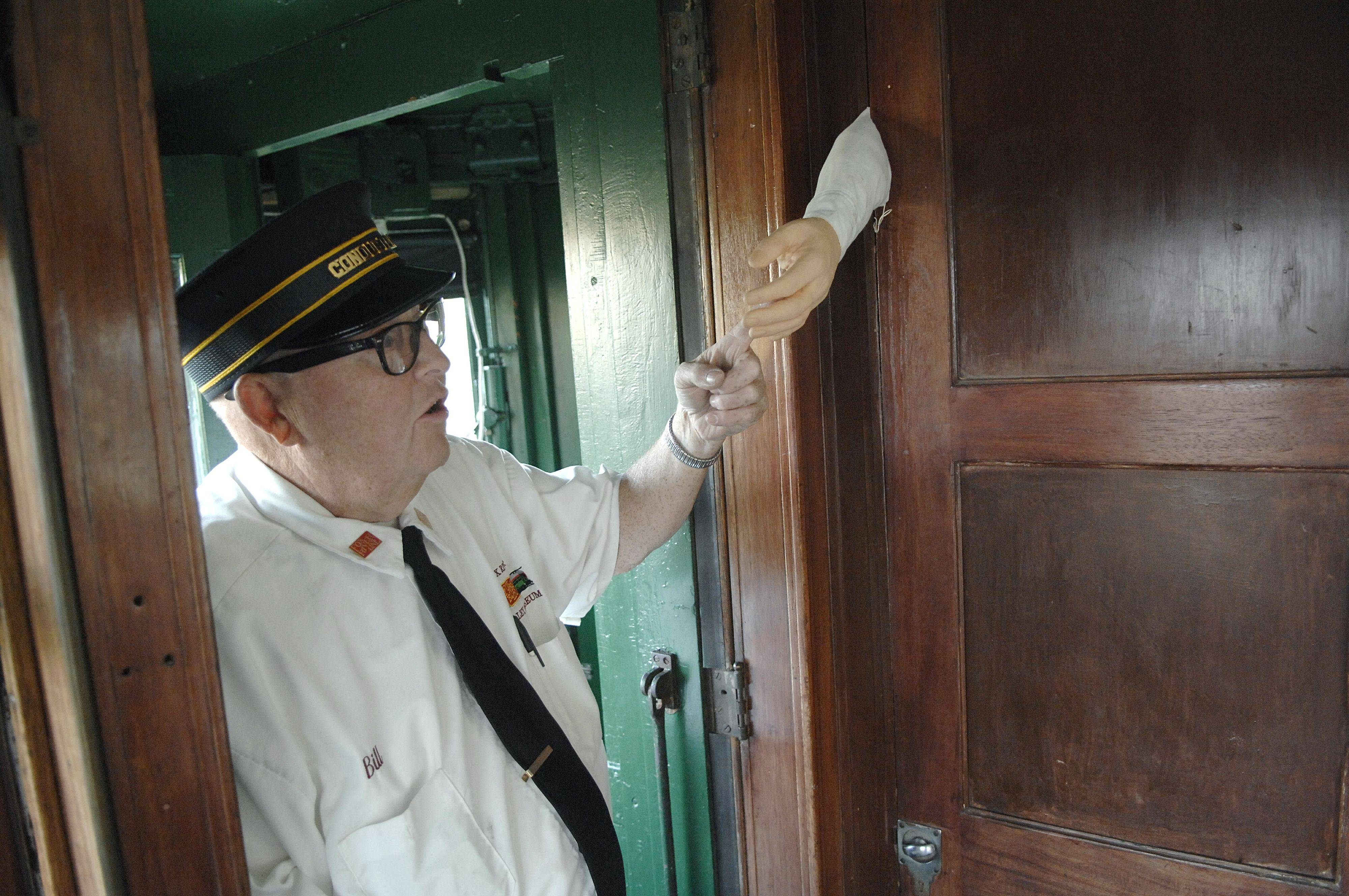 Motioning to a hand hanging out of a closet, Fox River Trolley Museum train conductor Bill Minerly warns children in the front seats what they do with those who badly behave on the Halloween Hiawatha Ghost Story Train. Minerly is from St. Charles.