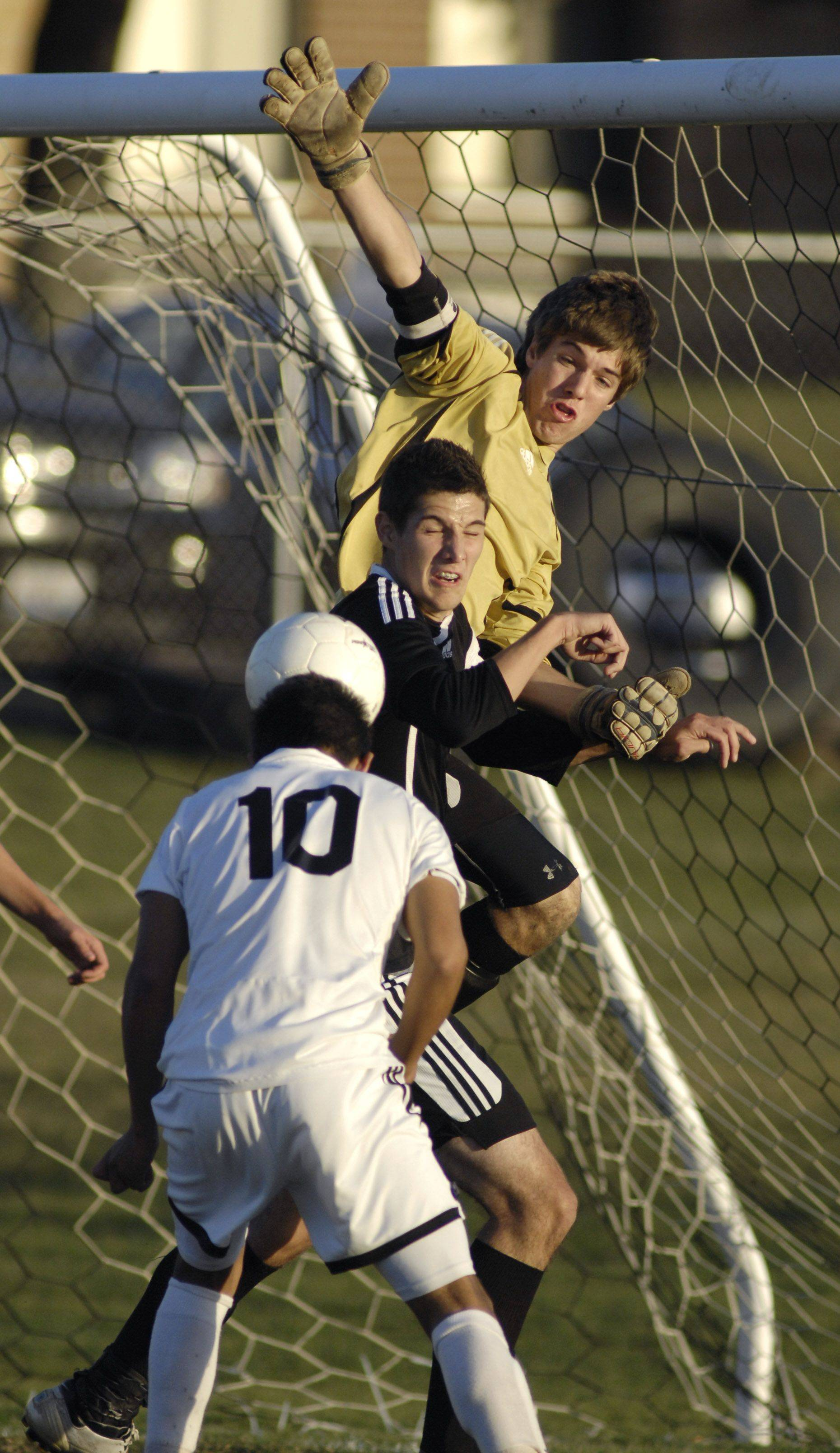 Sycamore's Justin David and goalie Jonathan Hamil block a header by Kaneland's Jordan Escobedo during Wedneday's regional match.
