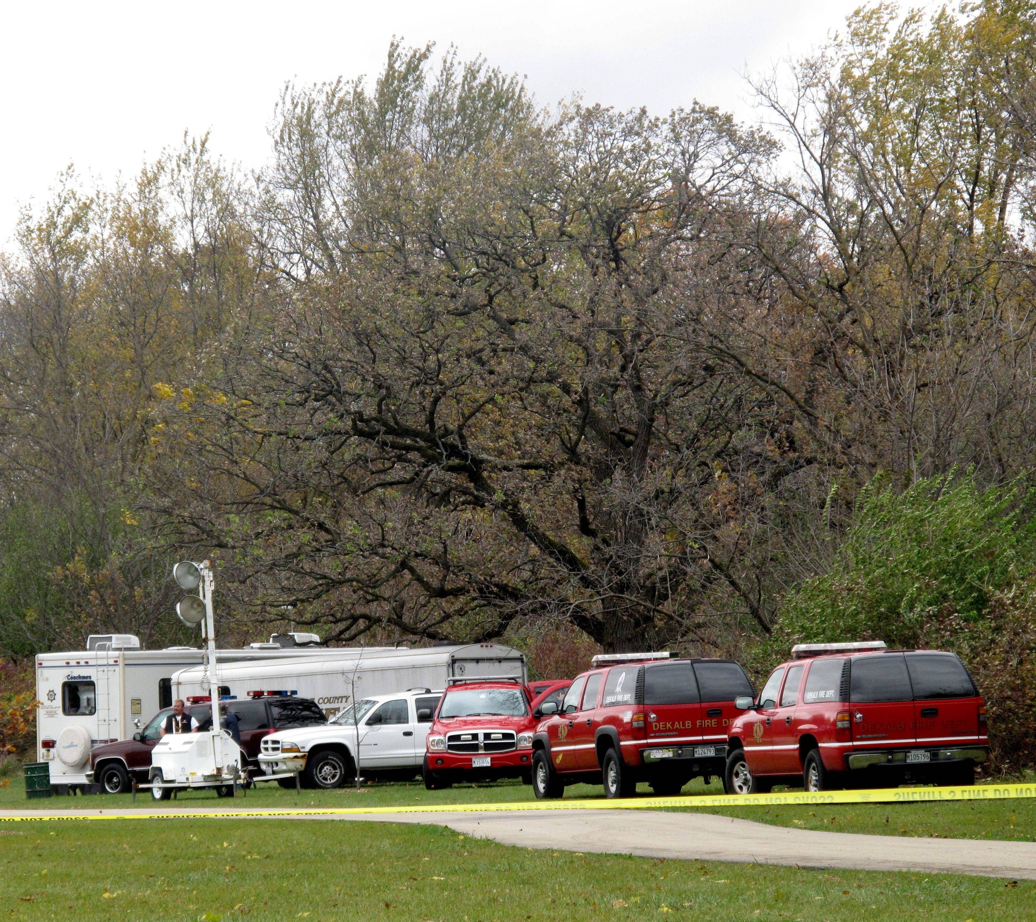 "Emergency vehicles sit Tuesday just off the nature path at Prairie Park in DeKalb where Antinette ""Toni"" Keller was last seen."