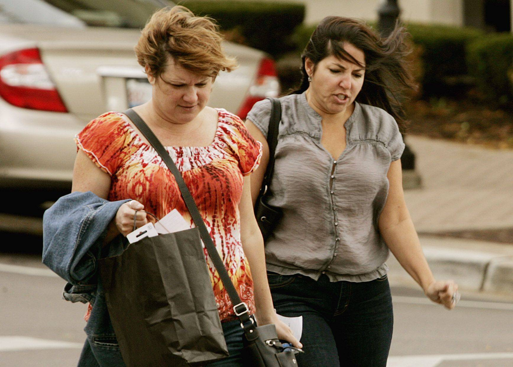 Charlee Hayes, left, and Getty Tune, both of Naperville, fight the wind Tuesday while walking along Jackson Street in downtown Naperville.