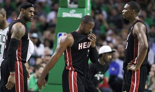 Miami Heat forward LeBron James, left, talks with teammates Dwyane Wade, center, and Chris Bosh, right, while trailing the Boston Celtics during the first half of an NBA basketball game in Boston, Tuesday.