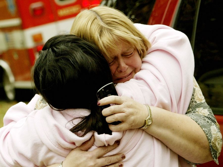 Jill Markussen, right, gets a hug from neighbor Tina Bibergall in front of her Wheaton apartment building, which was damaged in a fire Thursday morning.