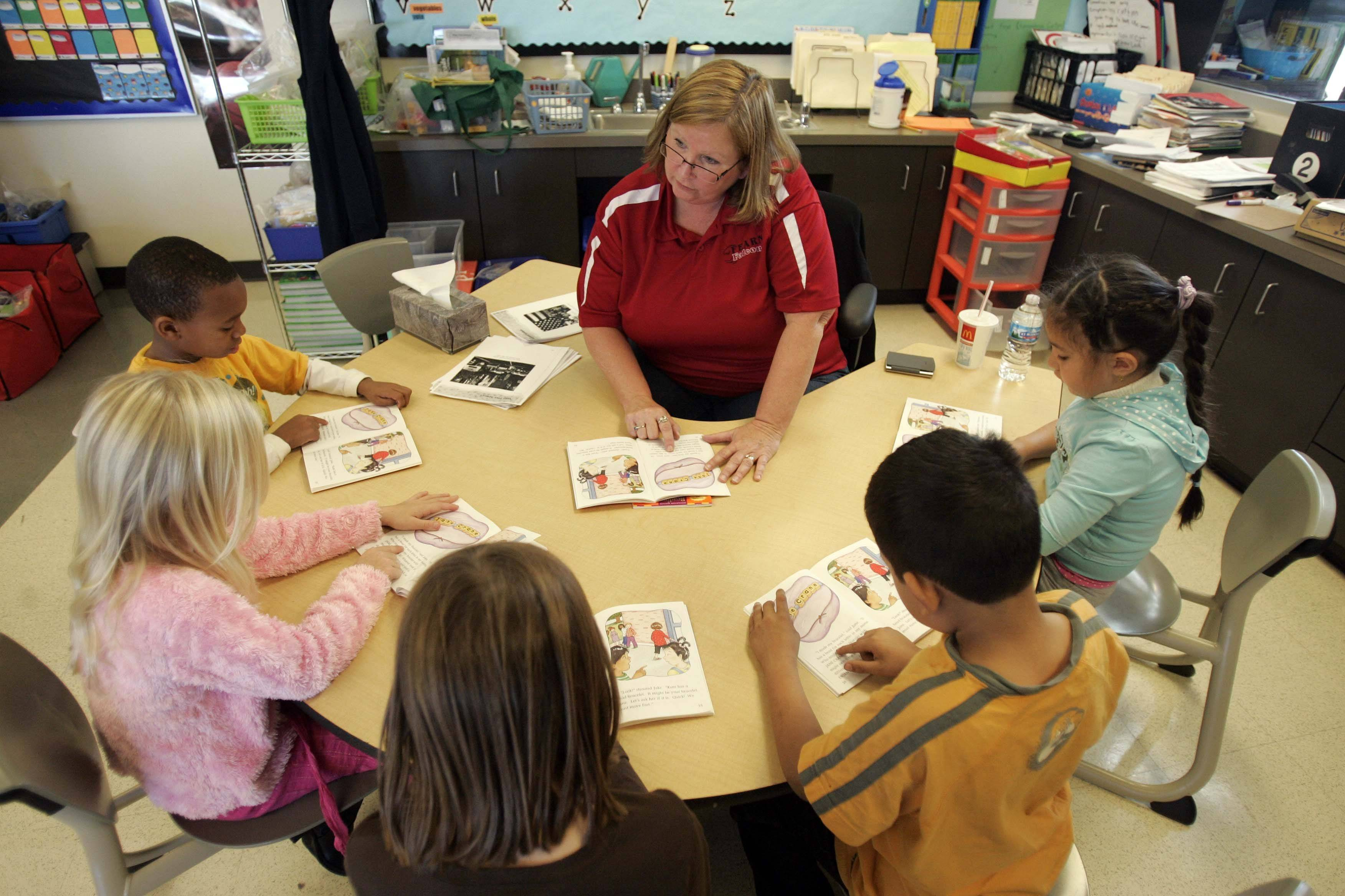 "Second-grade teacher Margaret King works with students at Harold G. Fearn Elementary School in North Aurora, which has made adequate yearly progress after being marked ""failing"" last year."