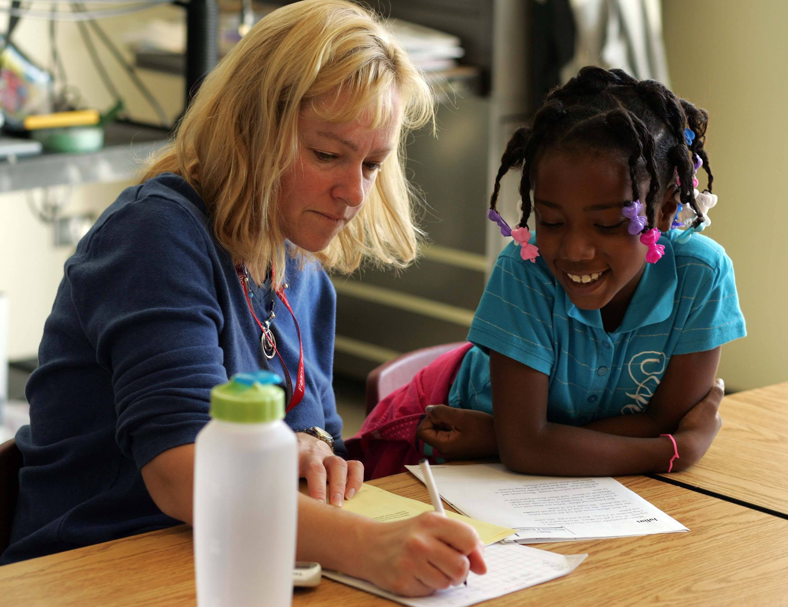 Seven-year-old Aaliyah Parker works with parent volunteer Cindy Rentes at Harold G. Fearn Elementary School in North Aurora. The school has added more individualized attention to kids having trouble to boost test scores.